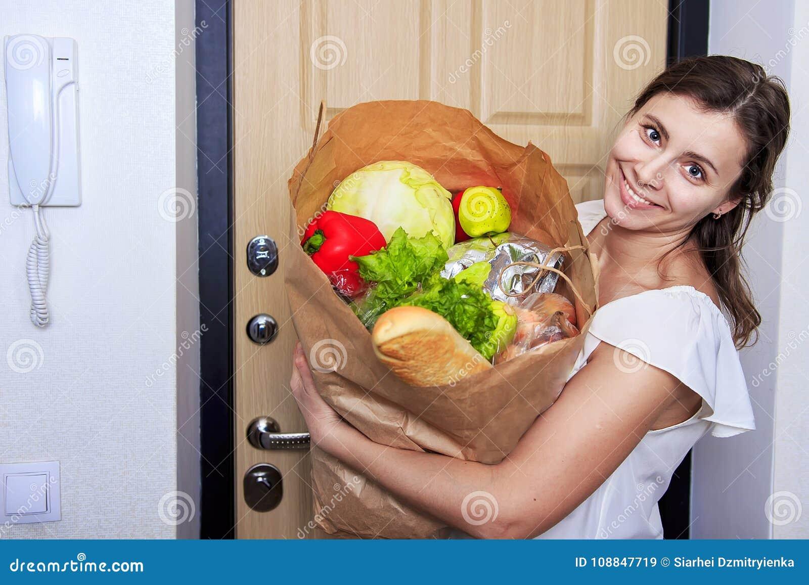 Молодая женщина держа сумку посещения магазина бакалеи с овощами Бумажное packege полно еды