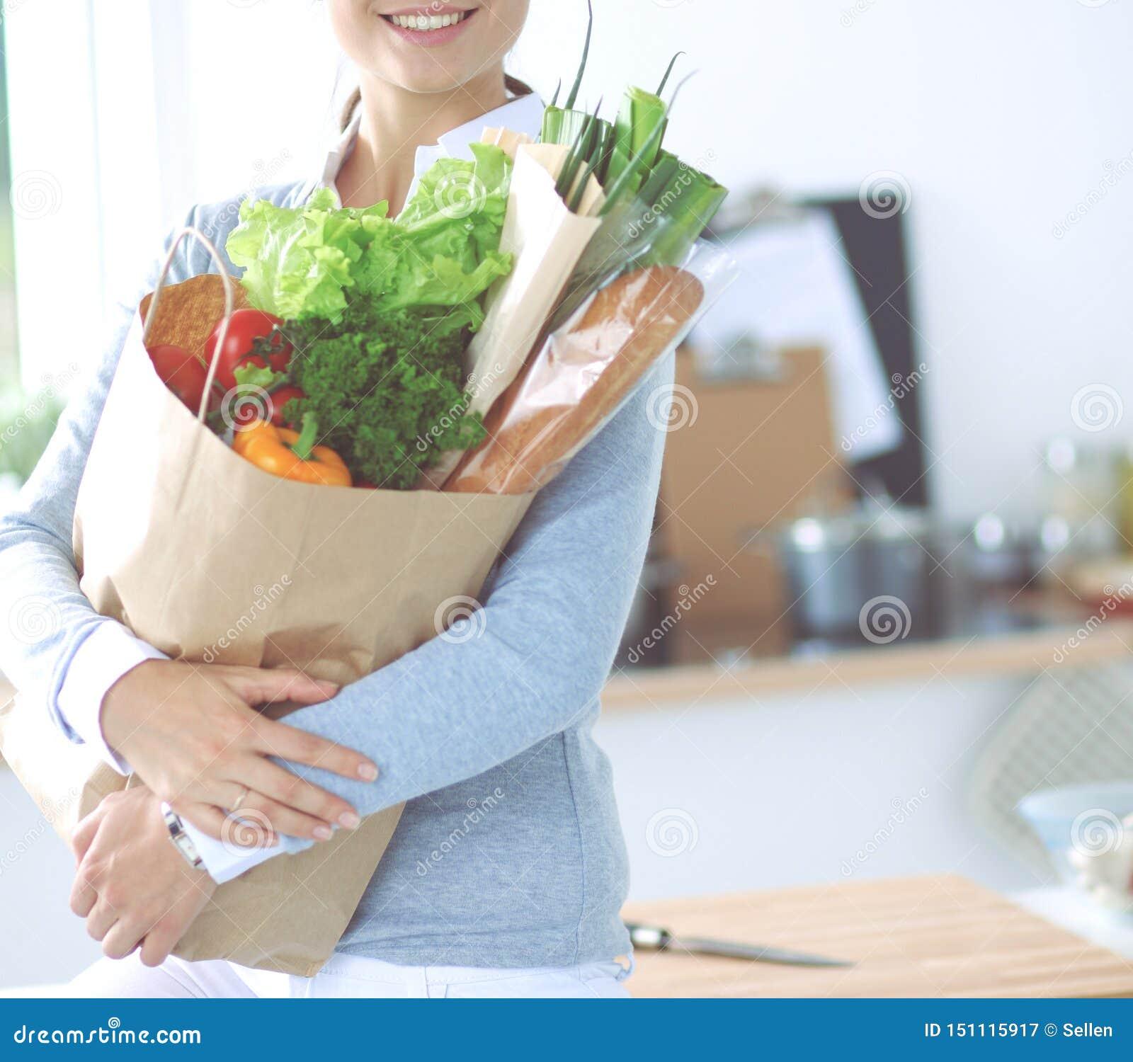 Молодая женщина держа сумку посещения магазина бакалеи с овощами Стоять в кухне
