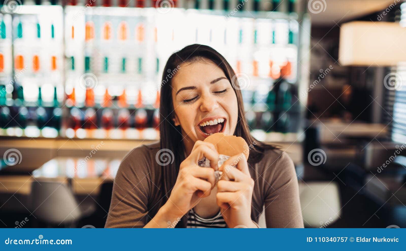 Молодая женщина есть наварный гамбургер Жаждая фаст-фуд Наслаждающся виновным удовольствием, есть высококалорийную вредную пищу У