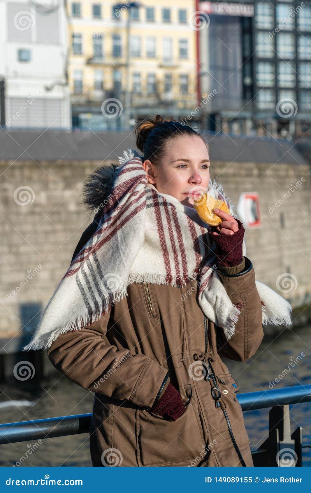 Молодая женщина есть северную немецкую закуску рыб еды на гавани Гамбурга