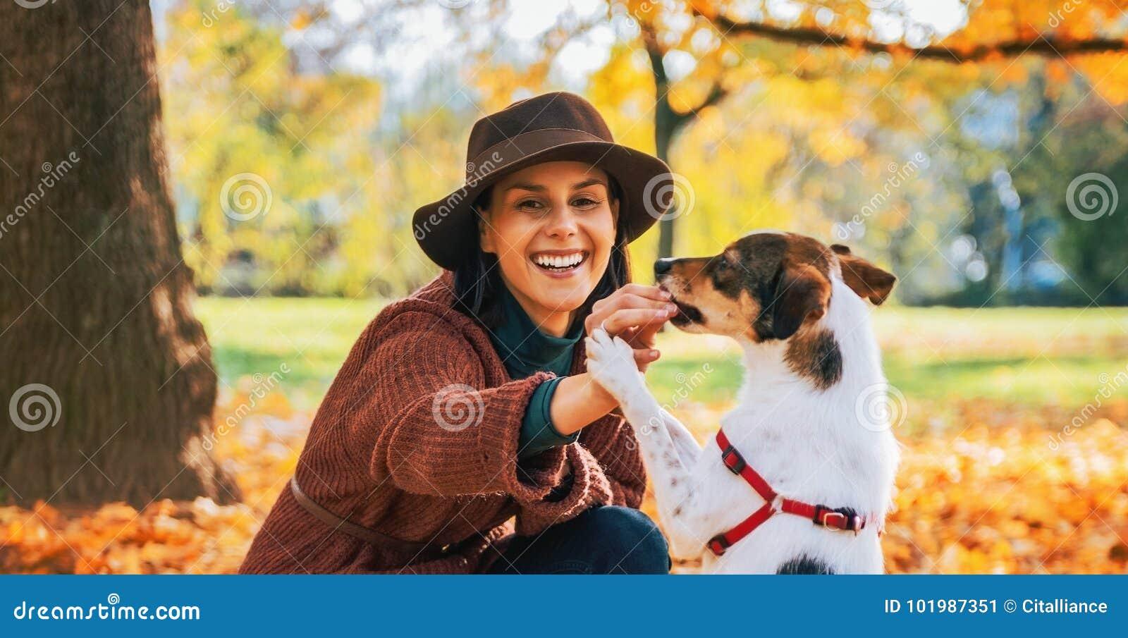 Молодая женщина играя с собакой outdoors в осени