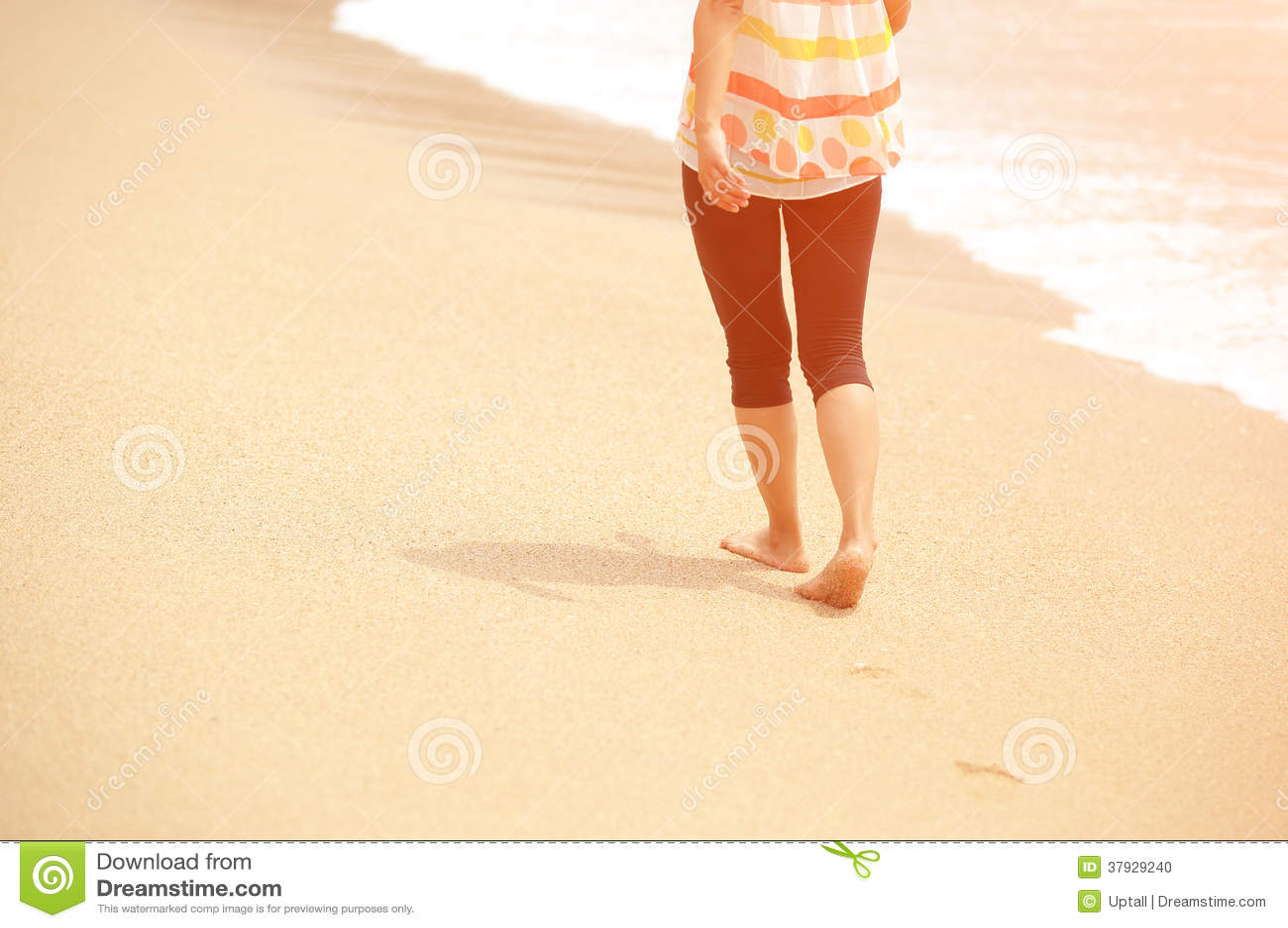 Молодая женщина идя на взморье