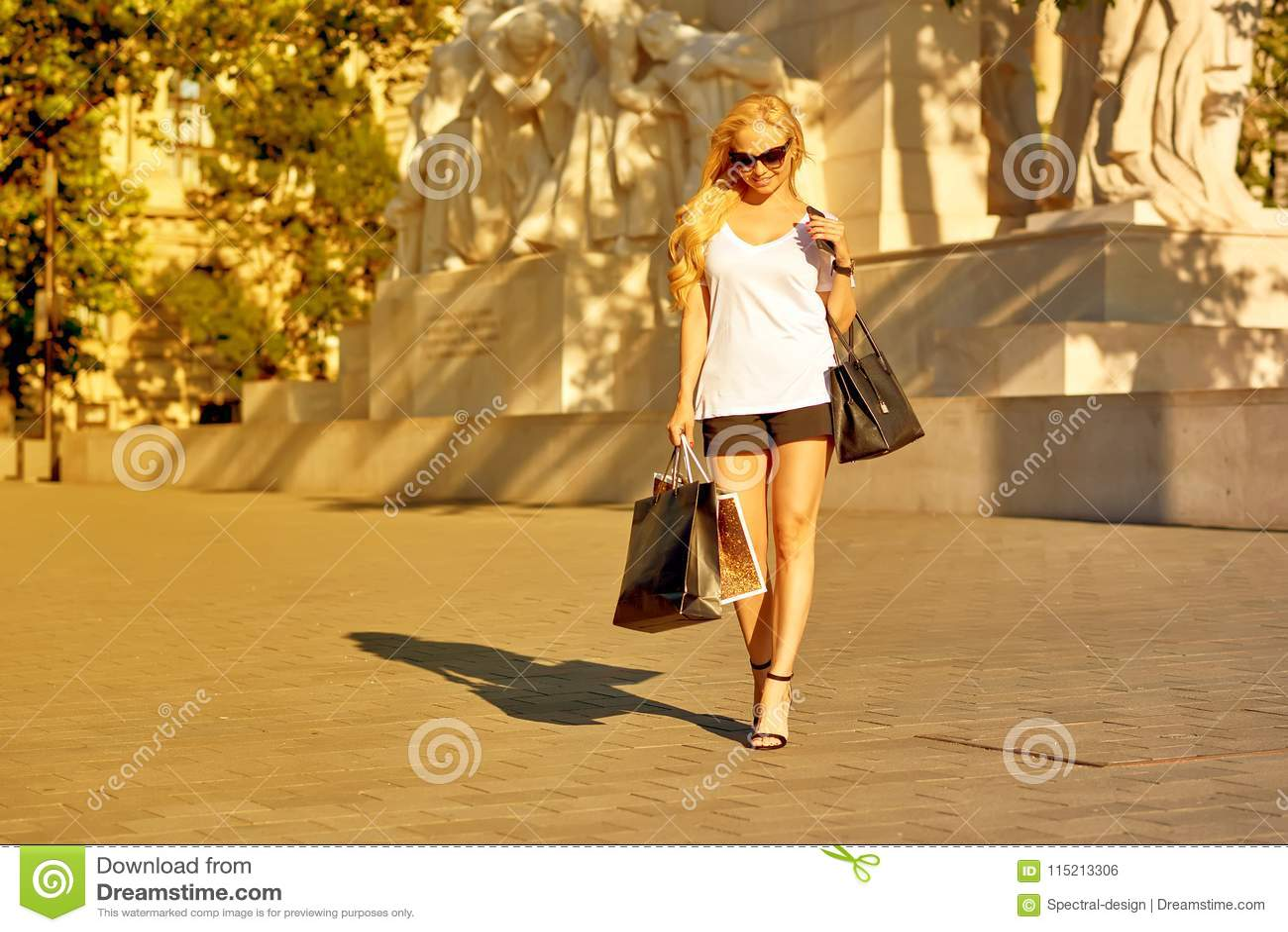 Молодая женщина идя с хозяйственными сумками в заходе солнца