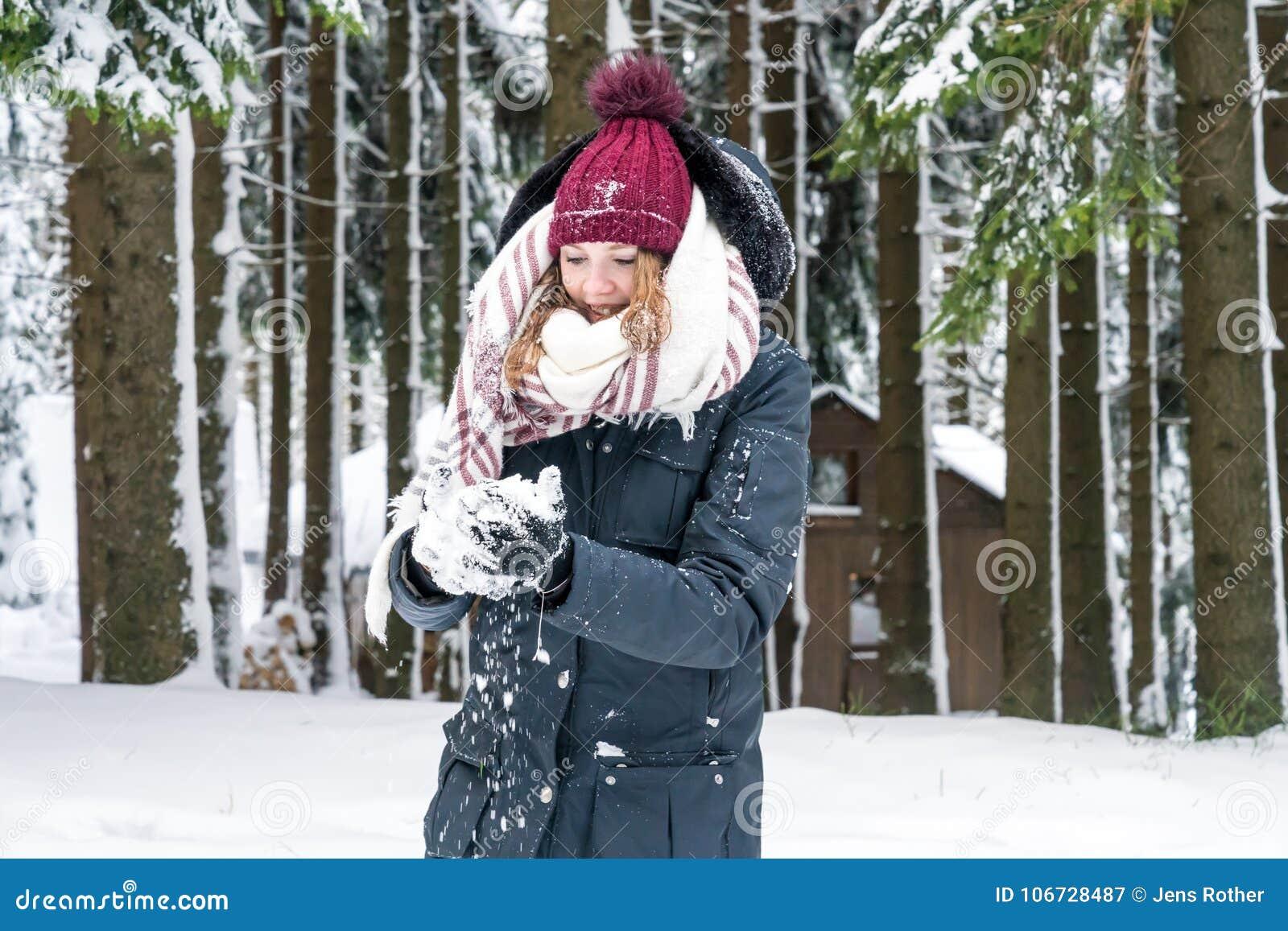 Молодая женщина имеет снежный ком в ее руке