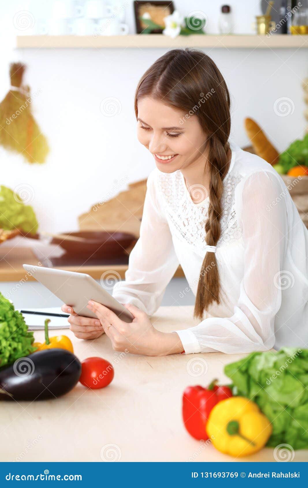 Молодая женщина используя таблетку пока варящ или делающ онлайн покупки в кухне девушка стороны камеры близкая смотря вверх здоро