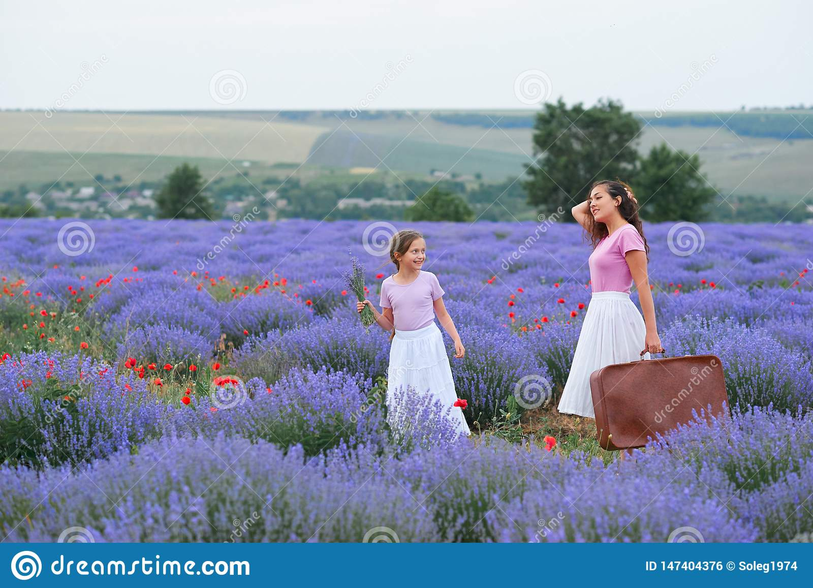 Молодая женщина и девушка идут через поле цветка лаванды, красивый ландшафт лета