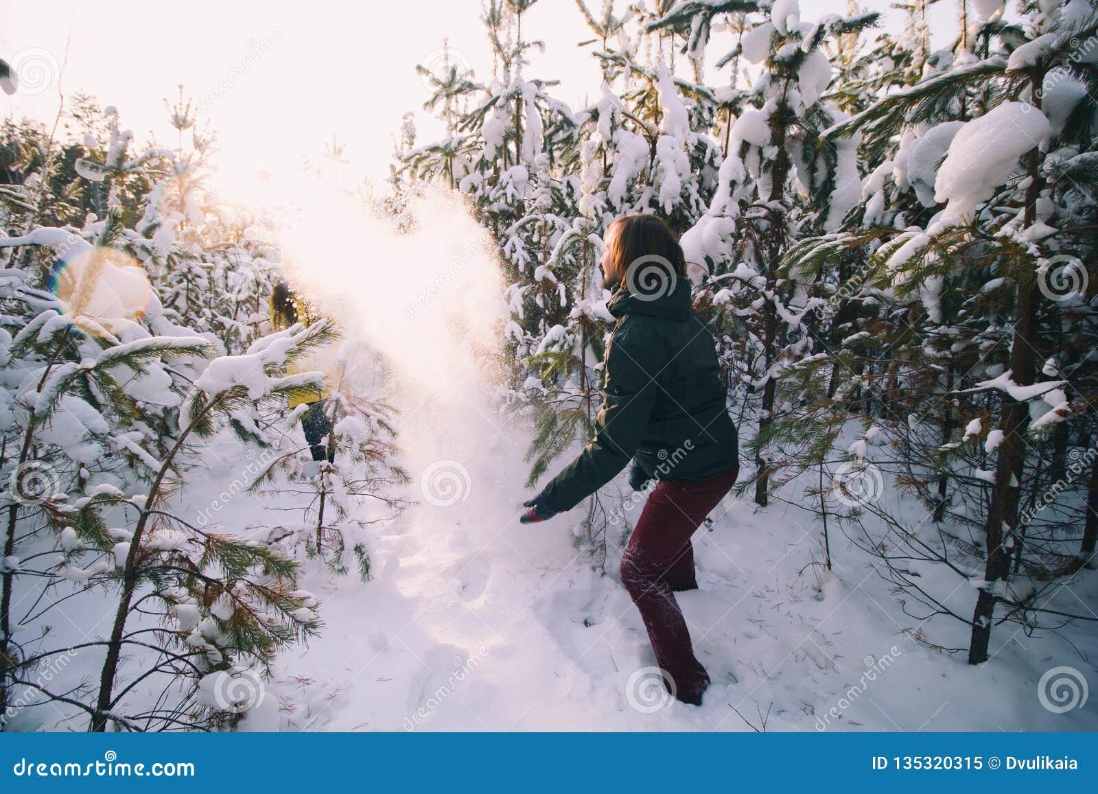 Молодая женщина и молодой человек играя снежные комья