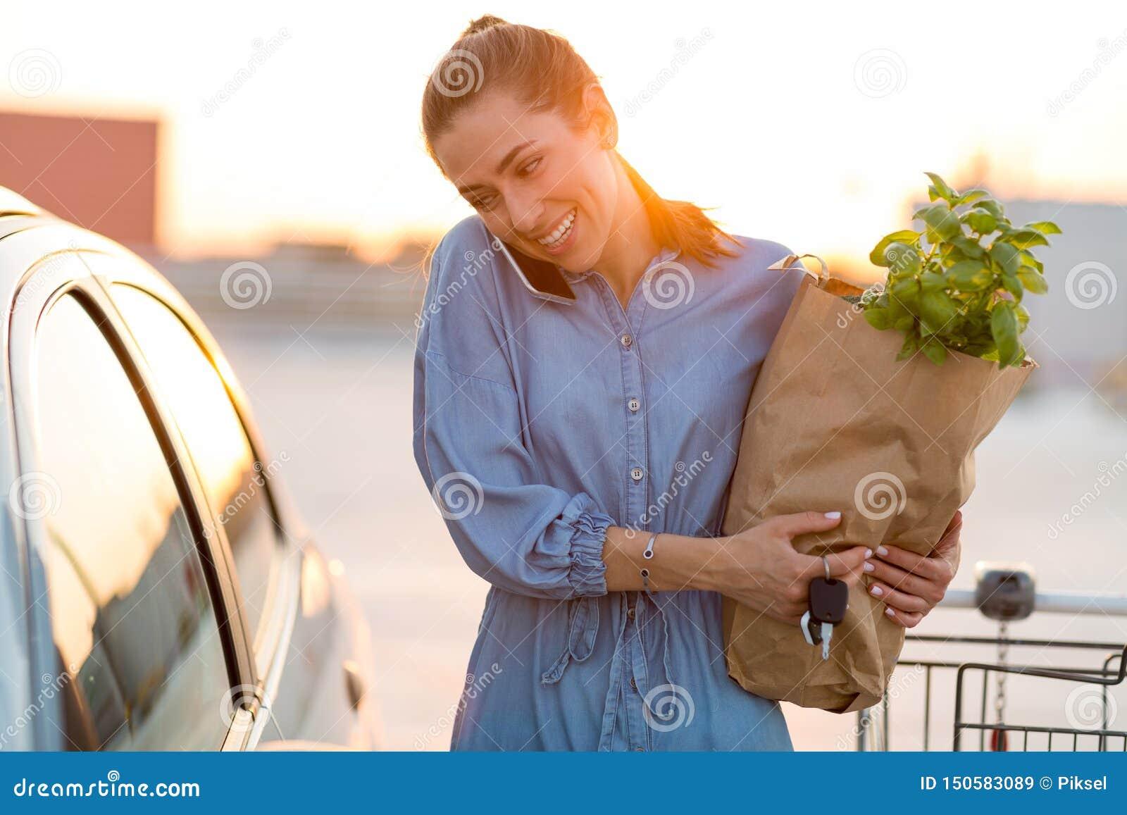 Молодая женщина кладя бакалеи на багажник автомобиля