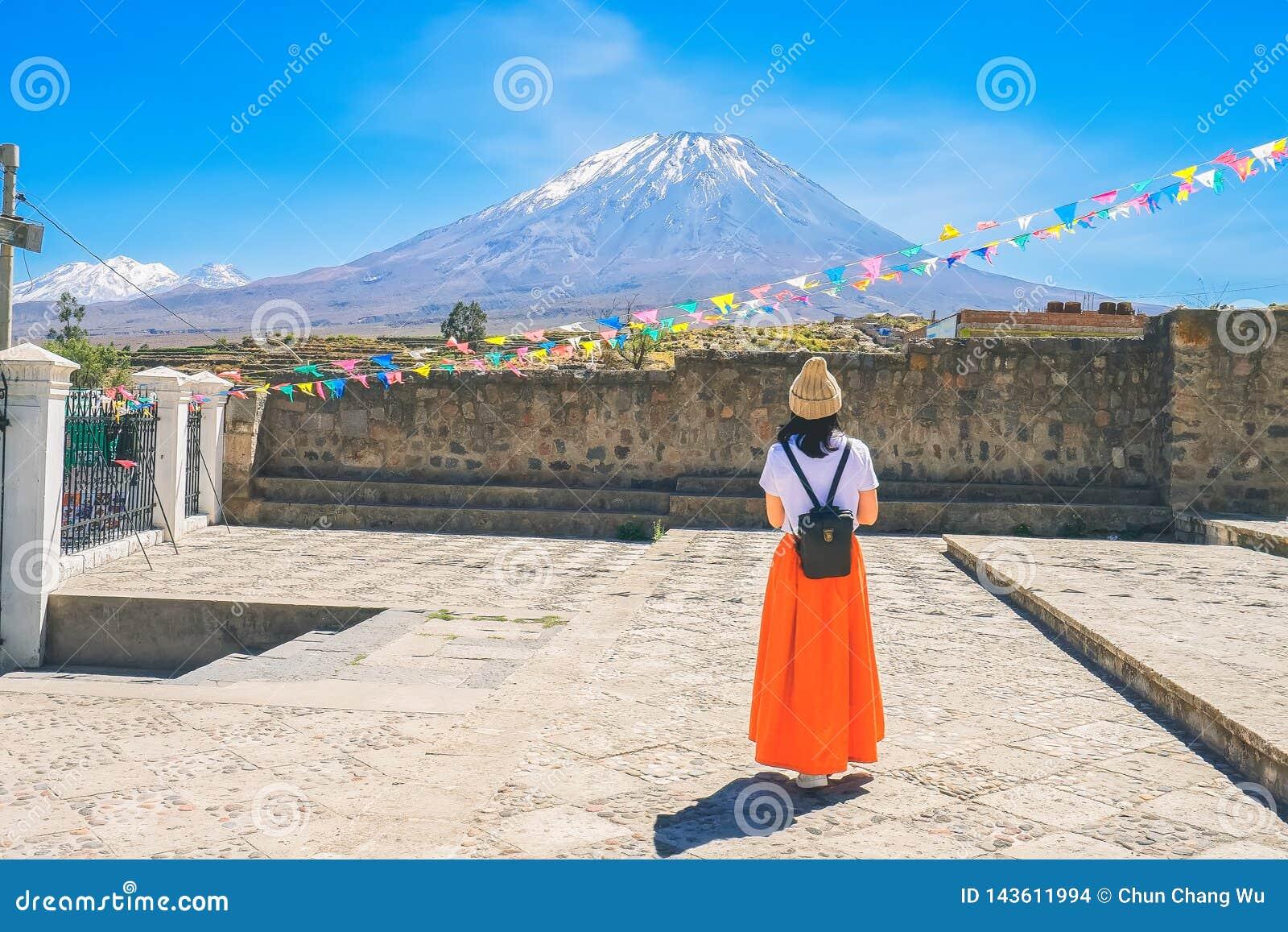 Молодая женщина которая носит крышку меха и оранжевую юбку восхищает вулкан El туманный в Arequipa, Перу