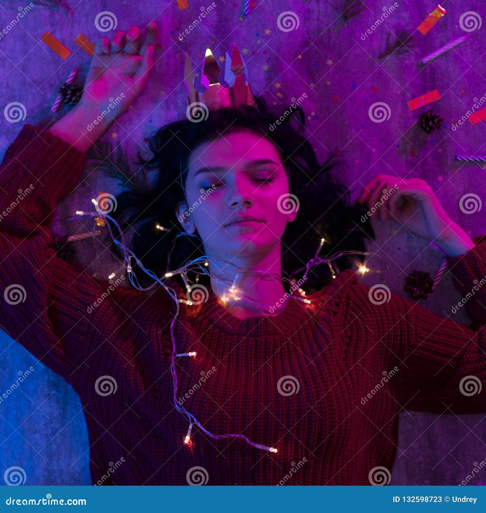 Молодая женщина лежа со светами торжеством xmas накаляя, рождеством, Новым Годом