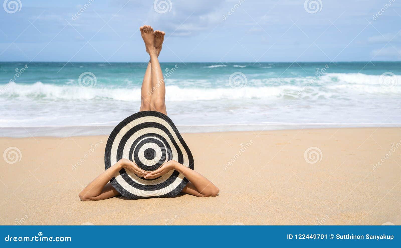 Молодая женщина моды ослабляет на пляже Счастливый образ жизни острова Белый песок, голубое облачное небо и море кристалла тропич