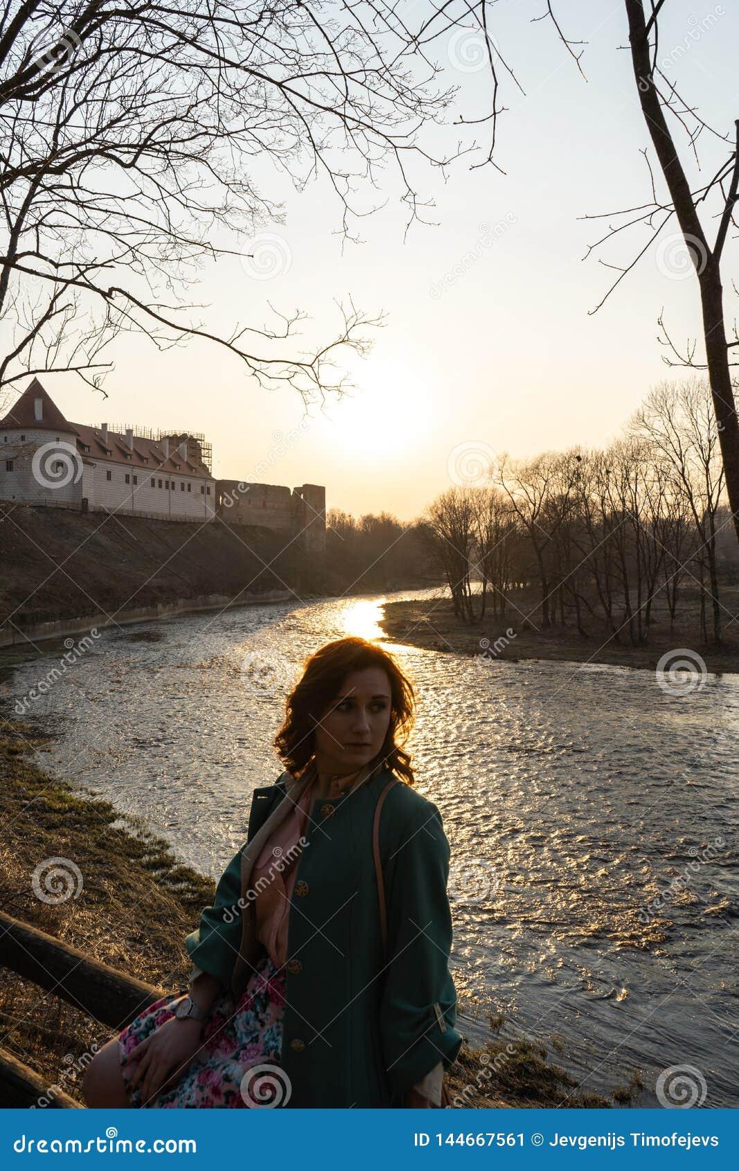 Молодая женщина моды ослабляя и наслаждаясь заход солнца около реки в