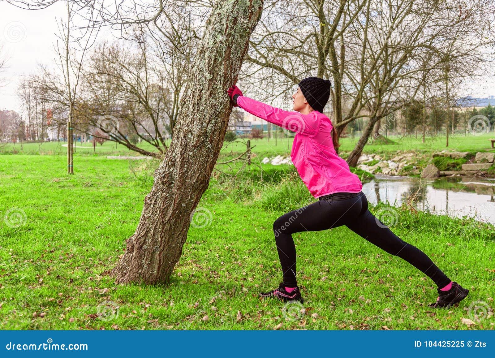 Молодая женщина нагревая и протягивая ноги перед бежать на холодной зиме, осень дня падения в городском парке