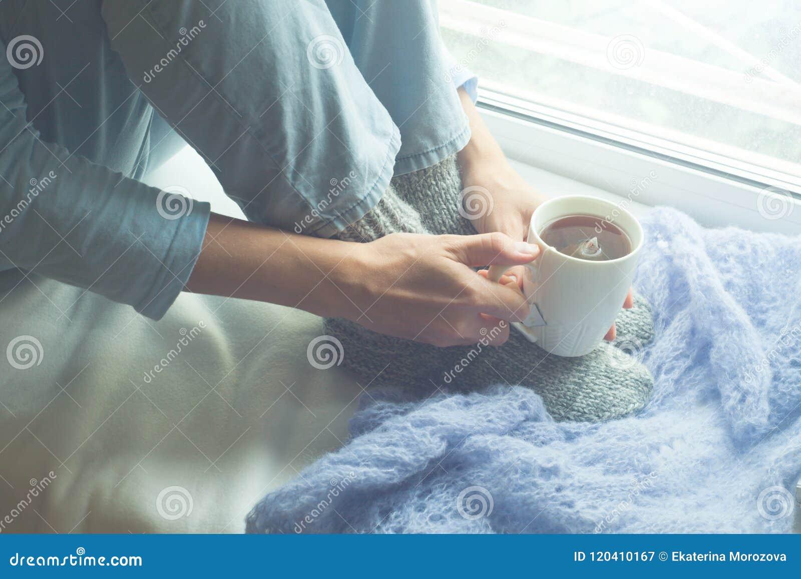 Молодая женщина наслаждаясь ее кофе или чаем утра, смотря вне окно Красивая романтичная непознаваемая девушка выпивая горячее пит