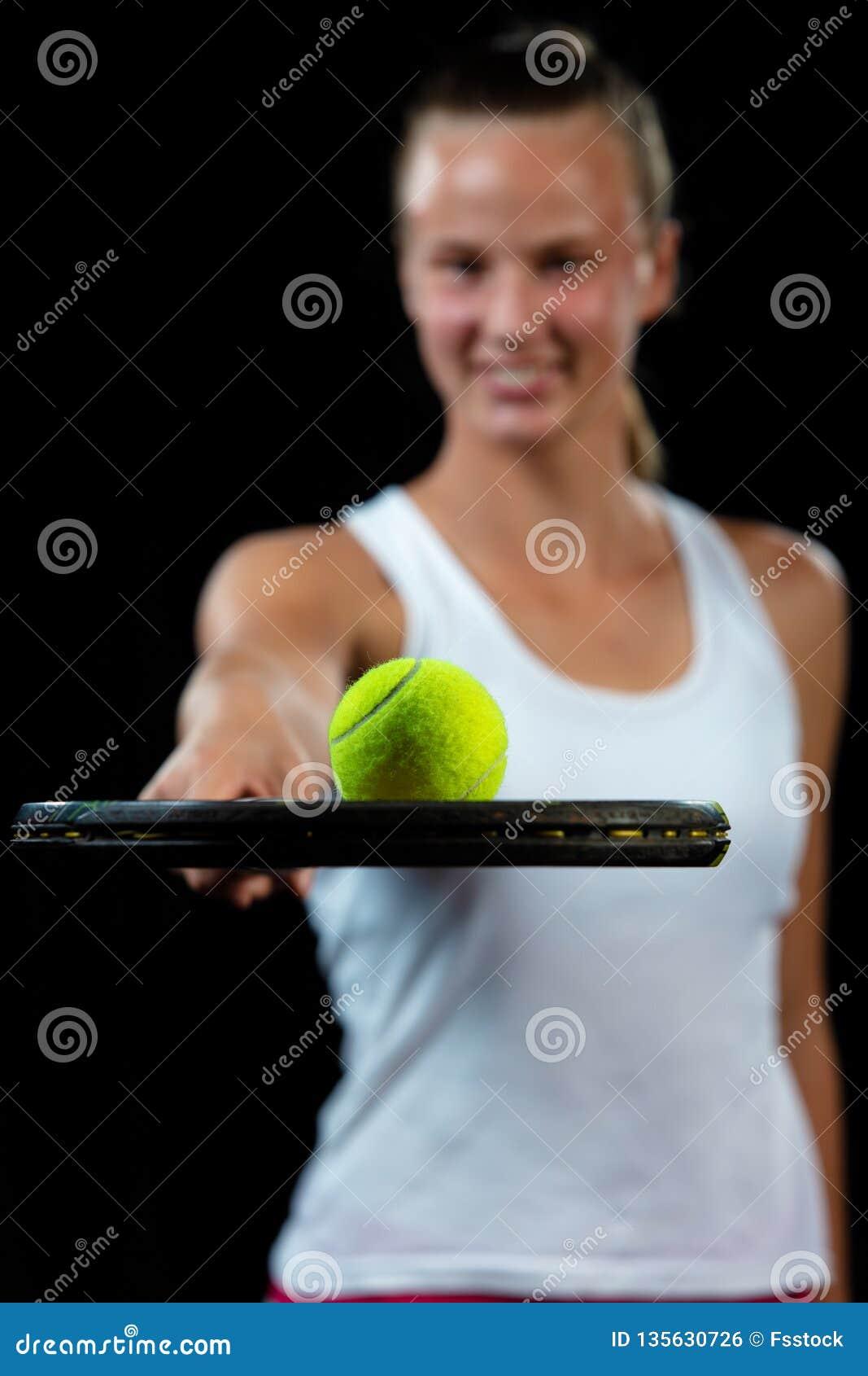 Молодая женщина на практике тенниса Игрок Beginner держа ракетку, уча основные умения портрет предпосылки черный