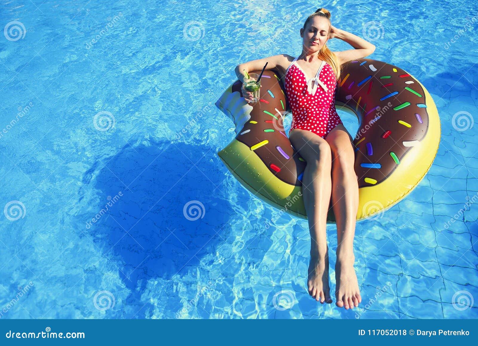 Молодая женщина на раздувном тюфяке в бассейне