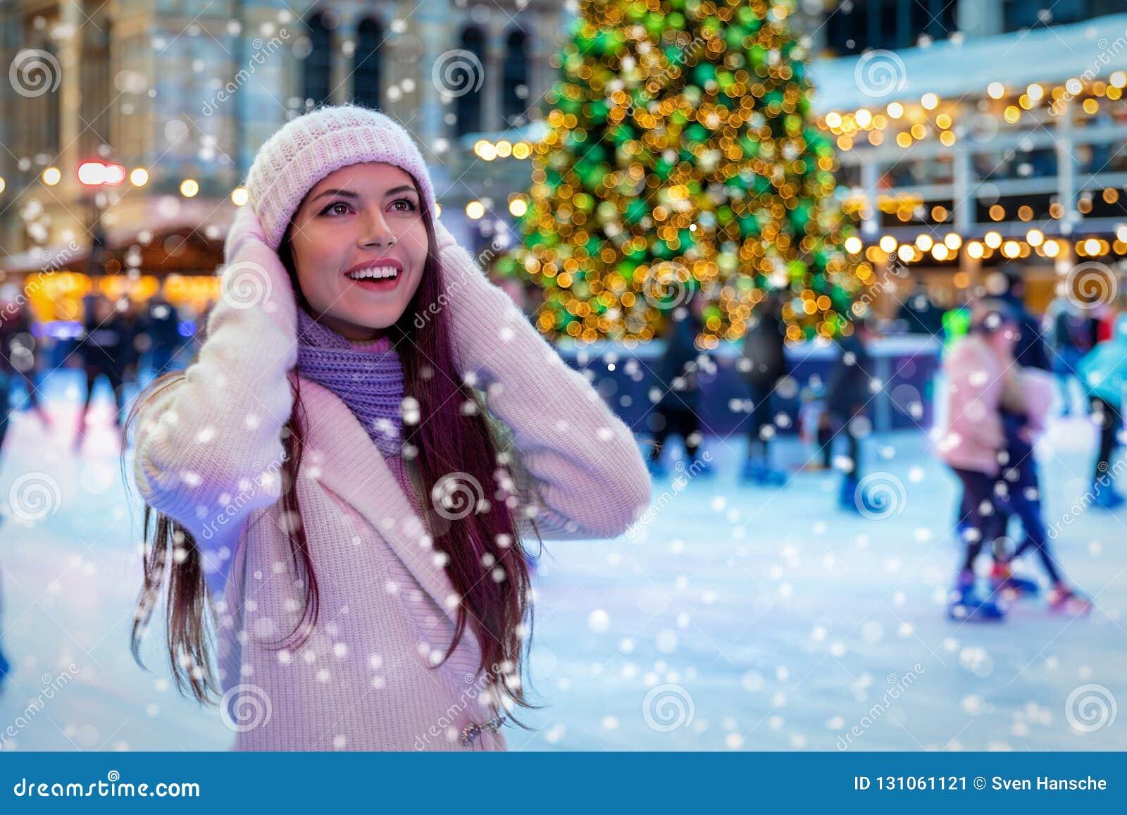 Молодая женщина на рождественской ярмарке наслаждается падая снегом