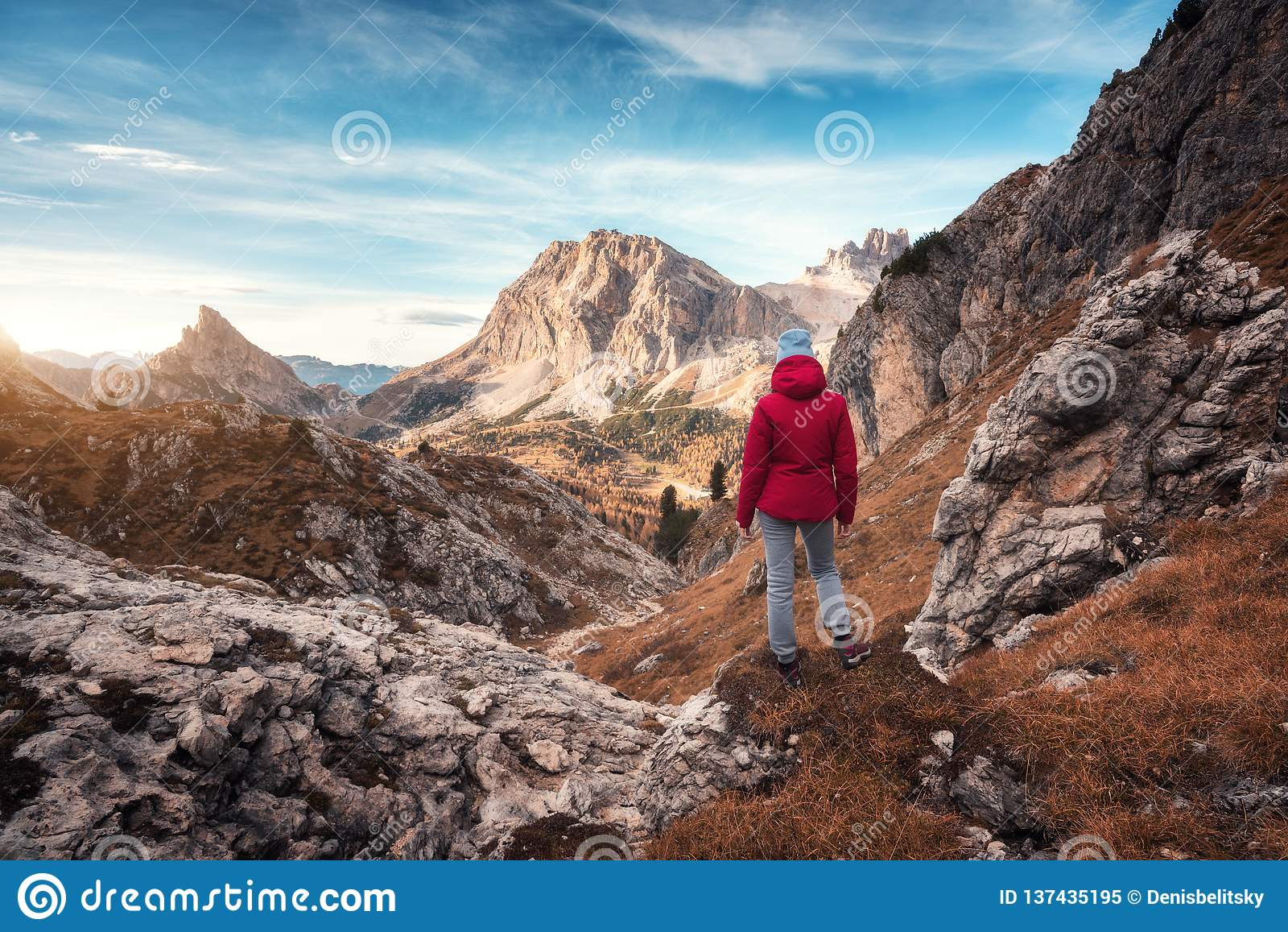 Молодая женщина на следе смотря на высоком горном пике на заходе солнца