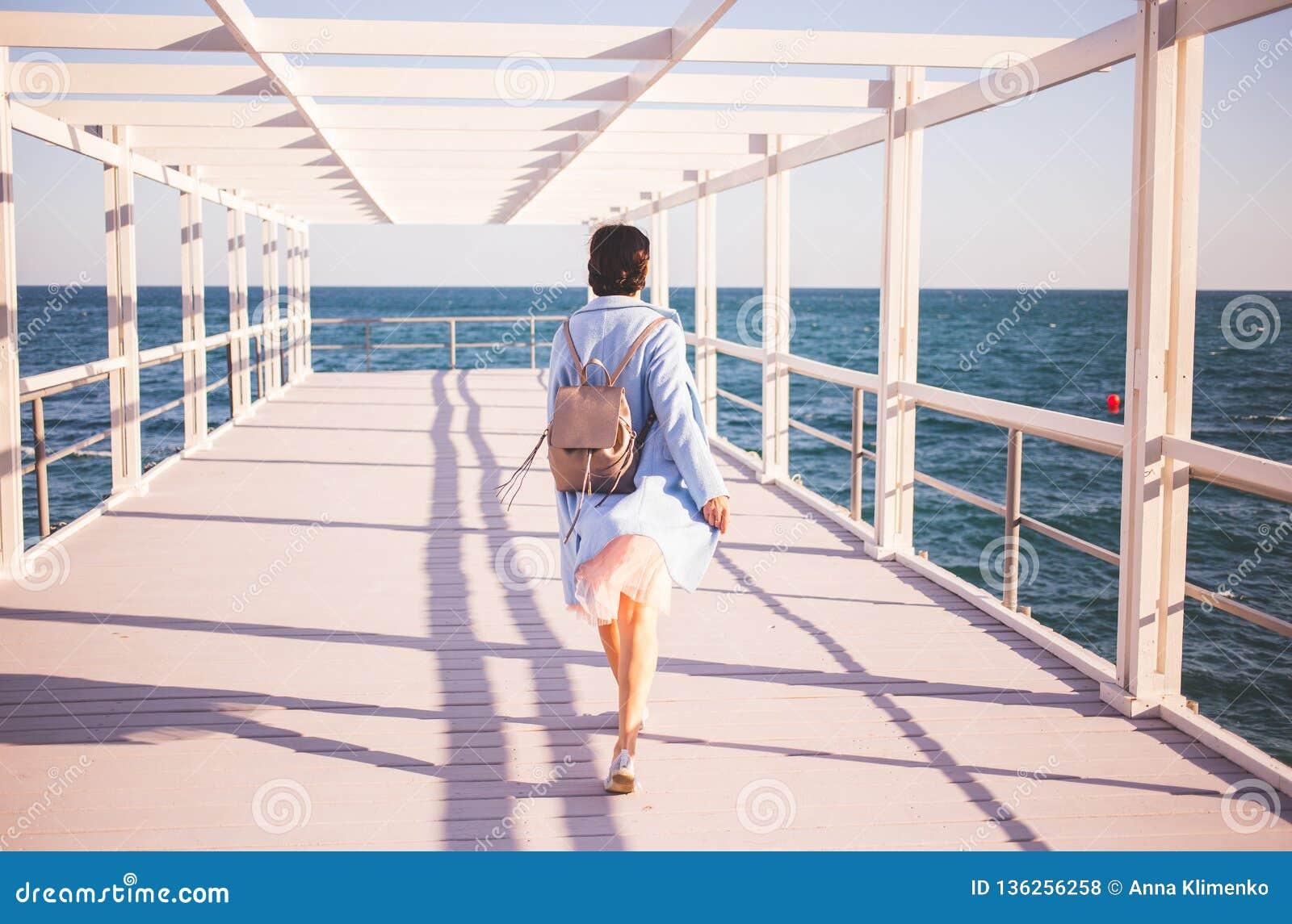 Молодая женщина нося голубое пальто идя около моря задний взгляд