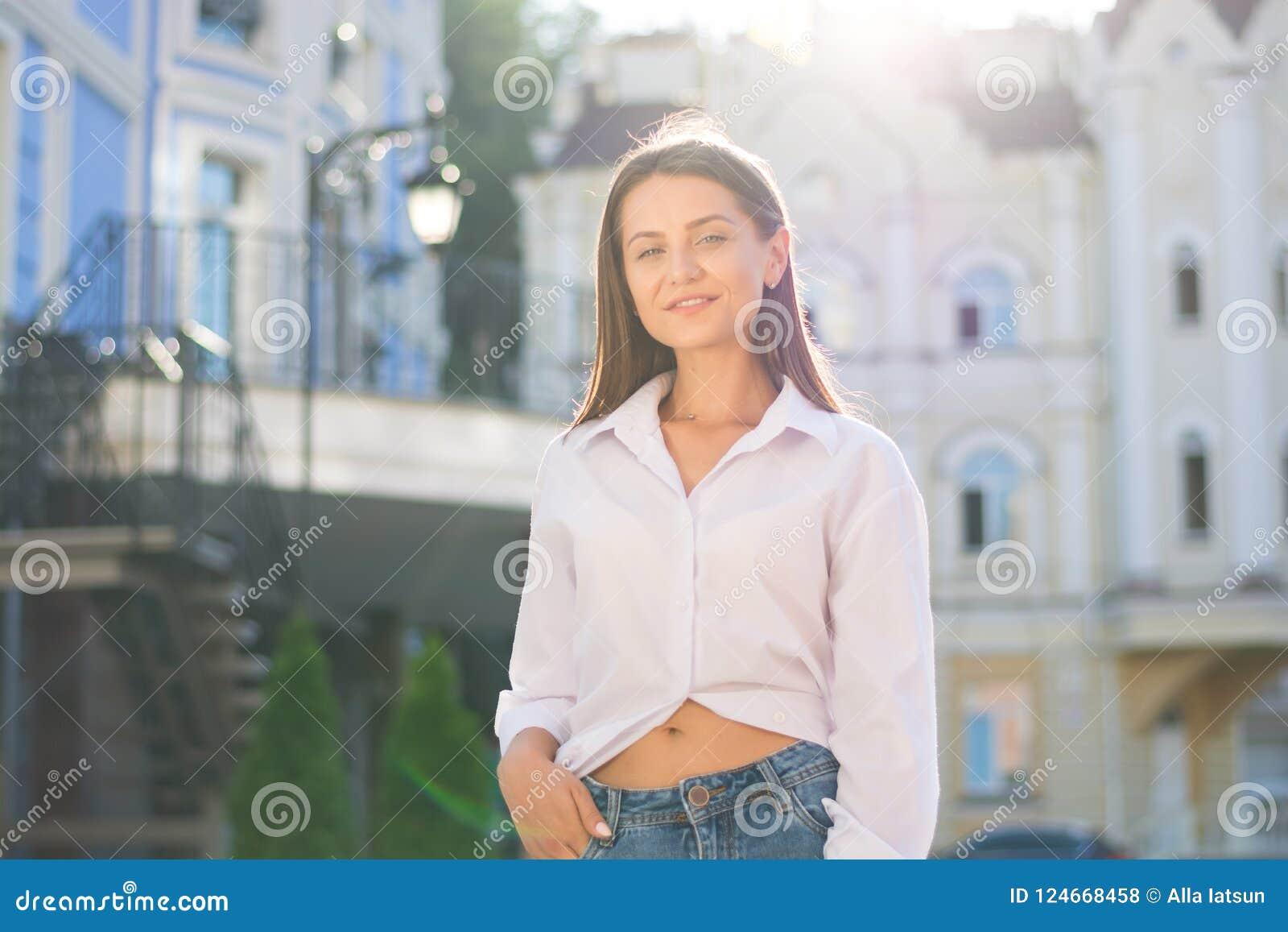 Молодая женщина, одетая в непринужденном стиле, стоит на str города