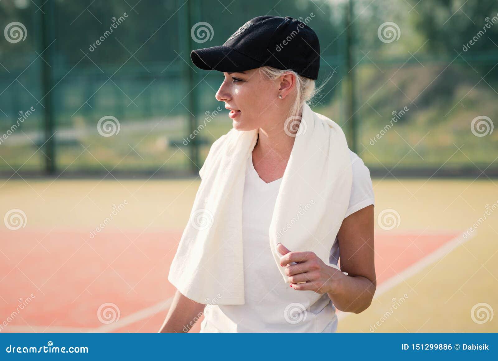 Молодая женщина отдыхая после делать спорт на теннисном корте r