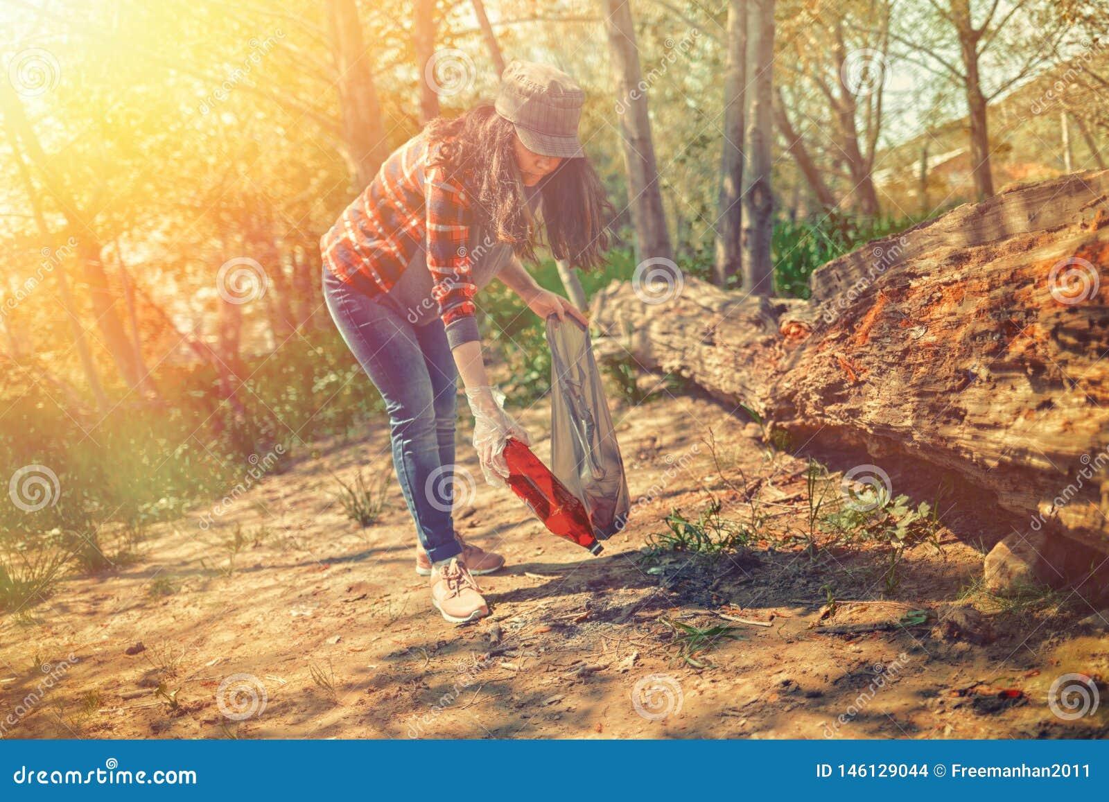 Молодая женщина очищает парк в субботу Консервация экологичности леса Подкраска