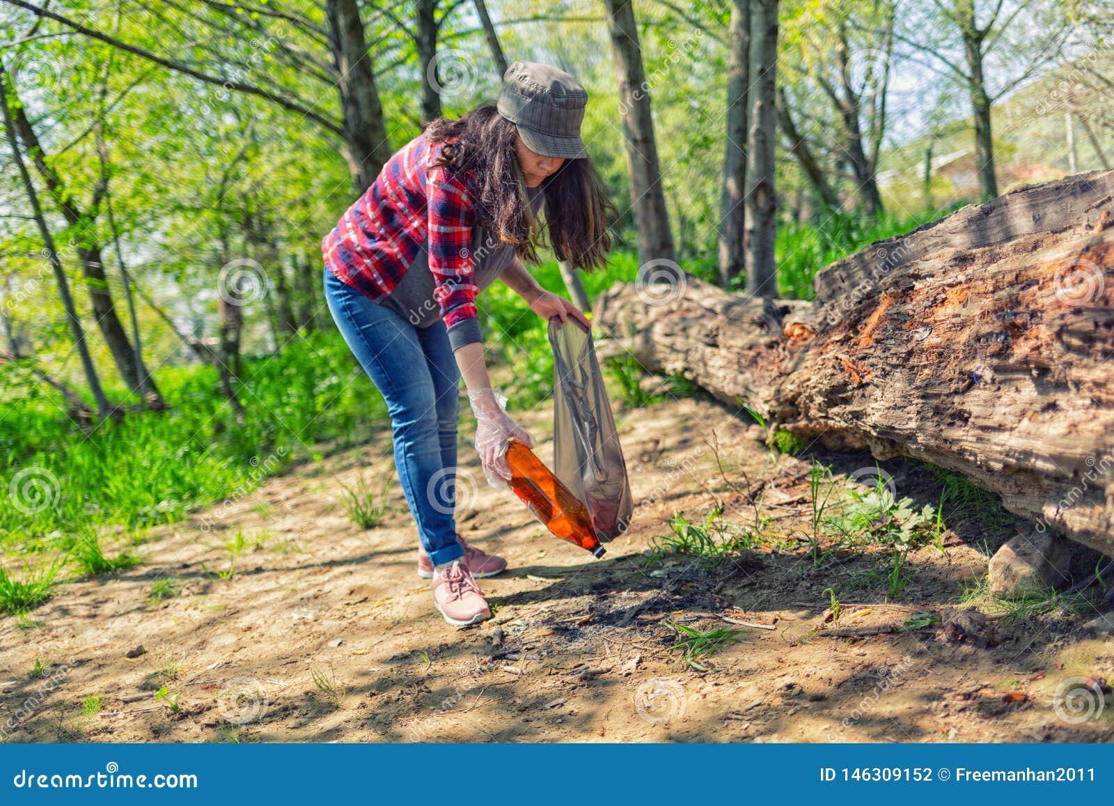 Молодая женщина очищает парк в субботу Консервация экологичности леса Eco