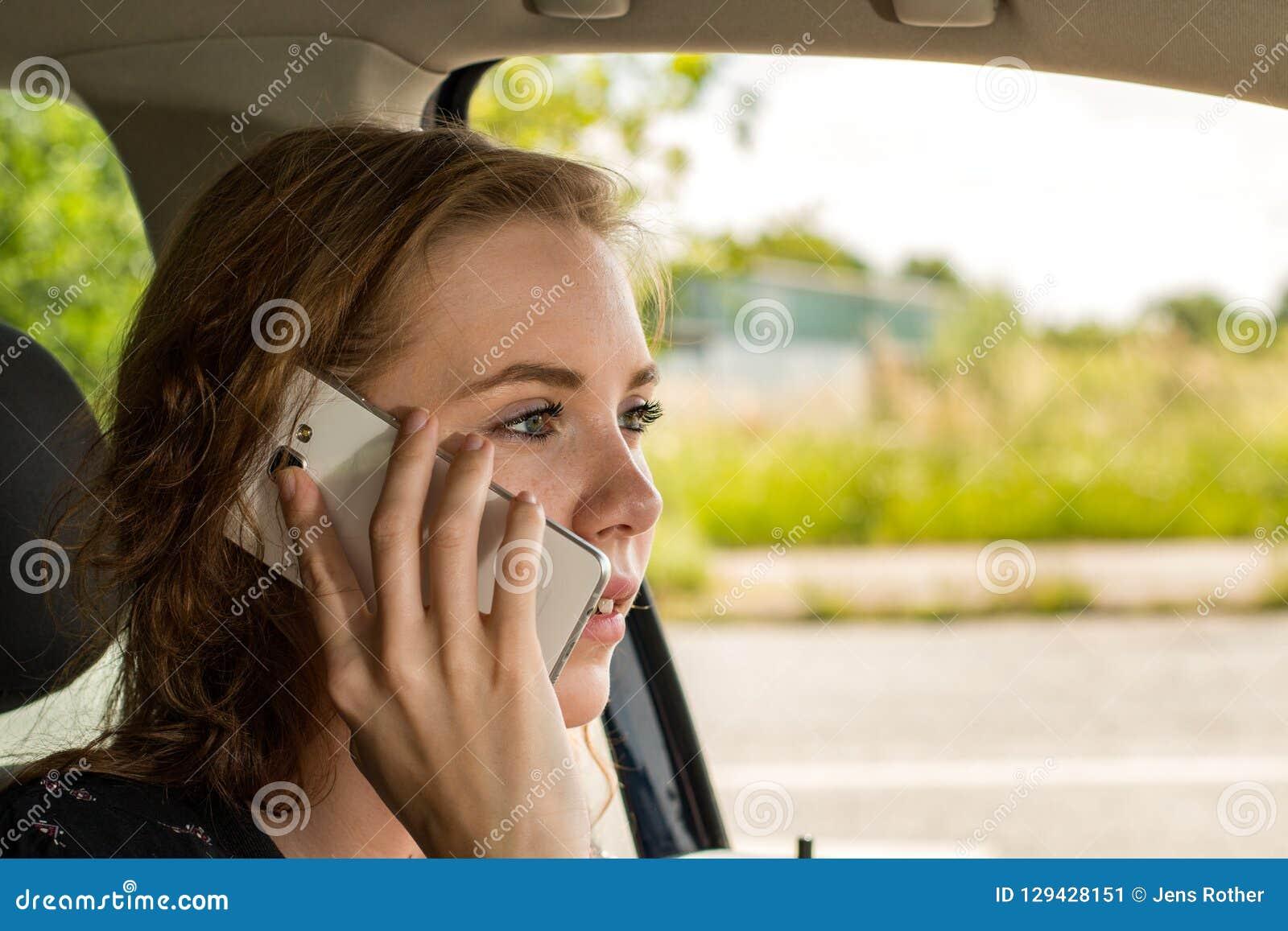 Молодая женщина по телефону пока управляющ и отвлечена