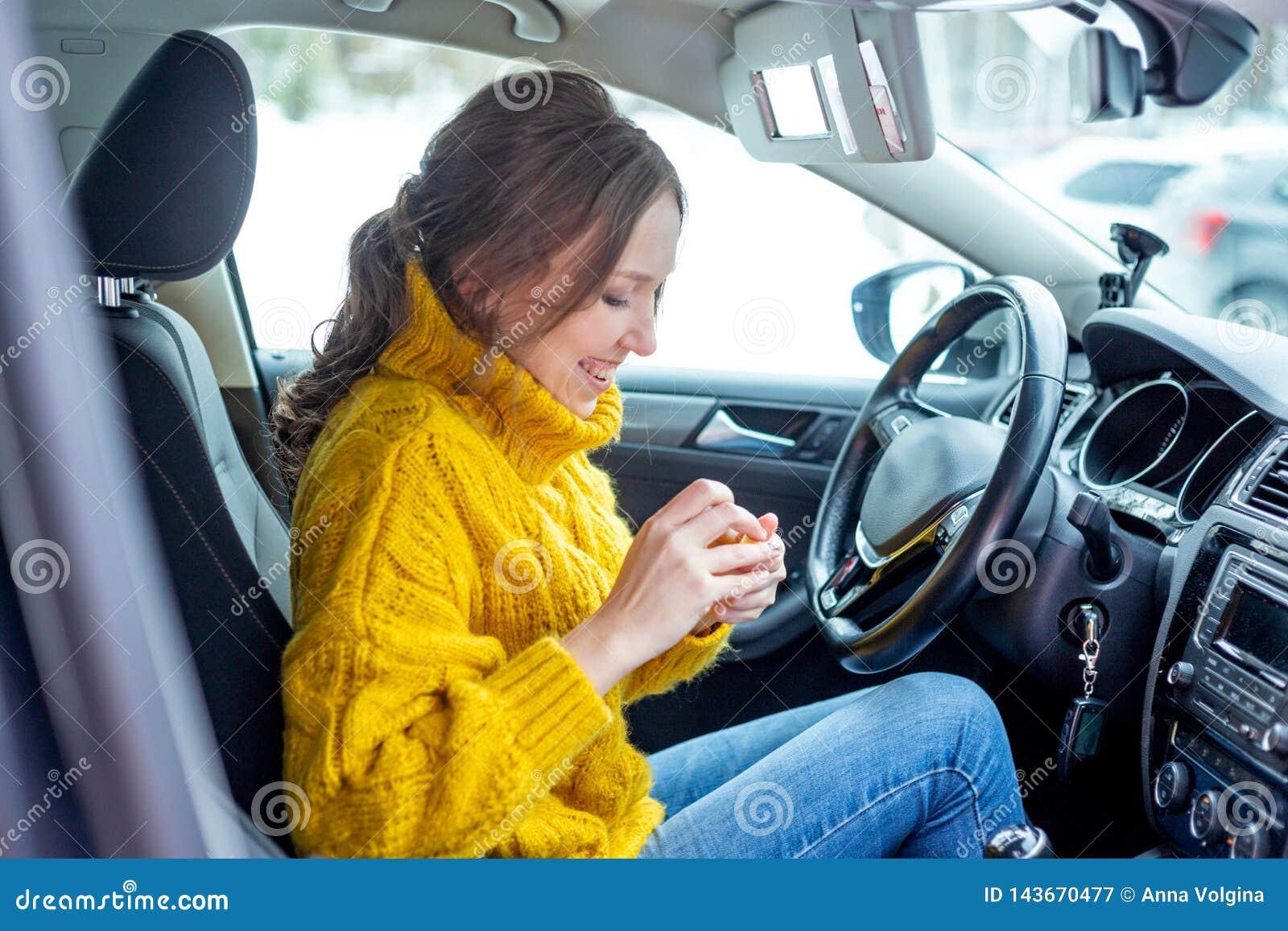 Молодая женщина прикладывая макияж в автомобиле
