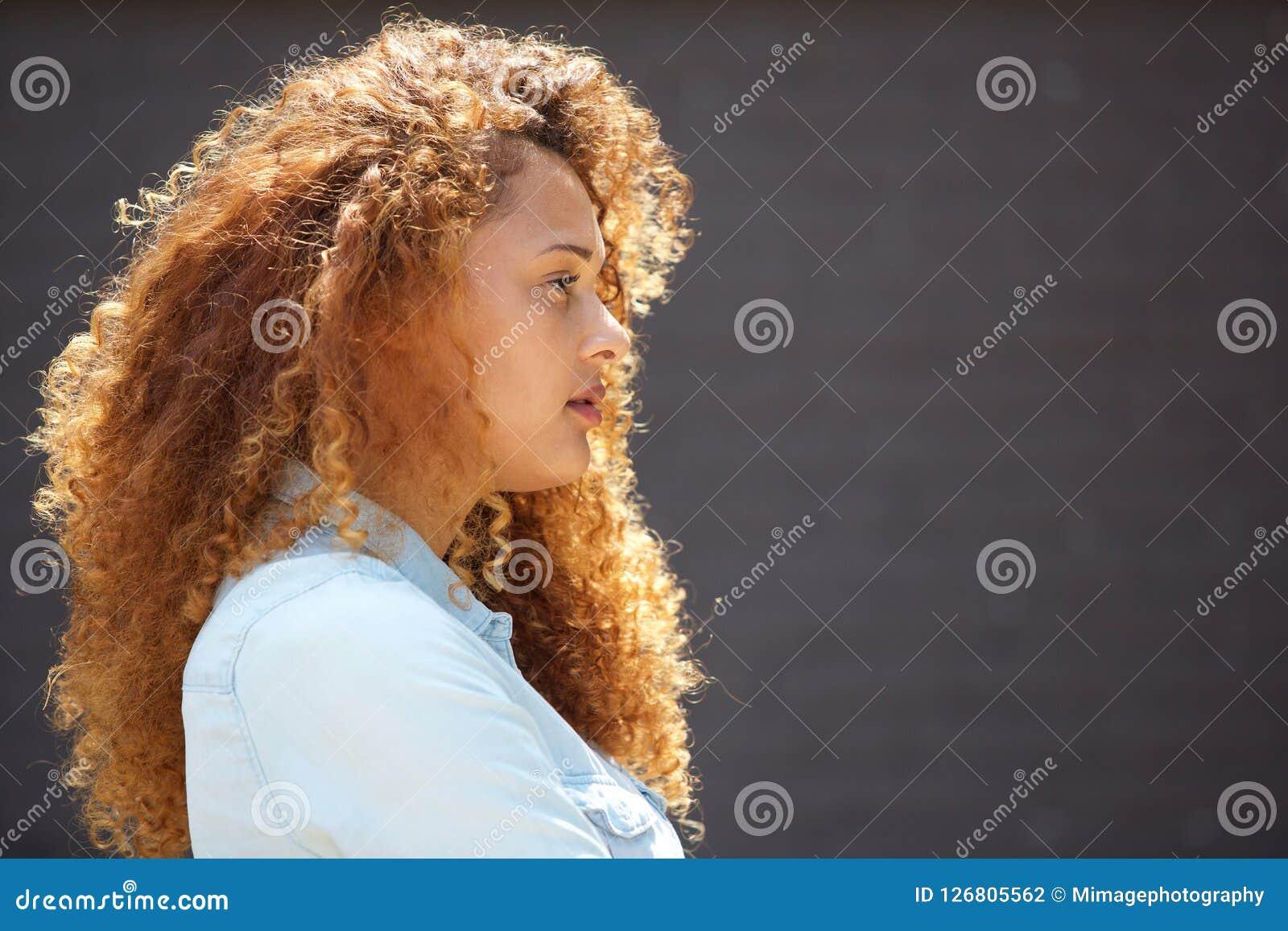 Молодая женщина профиля с вьющиеся волосы против серой стены