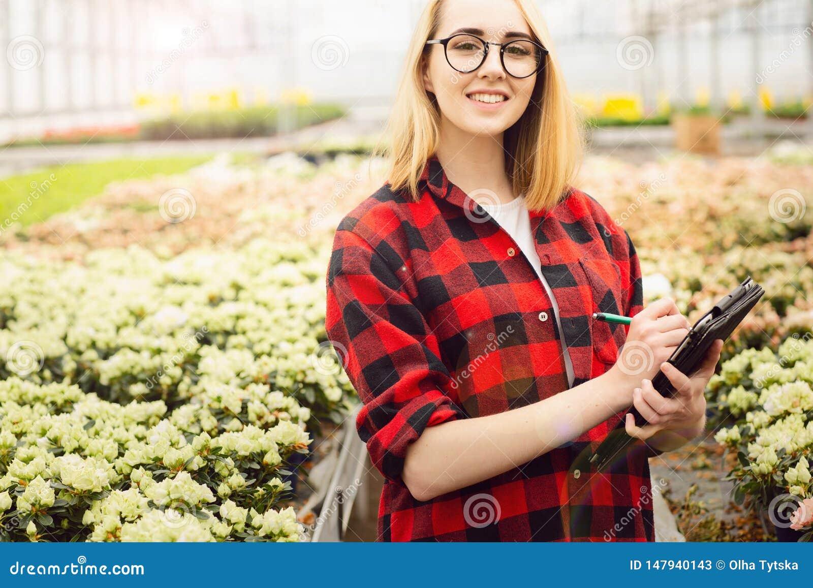 Молодая женщина работая в парнике Привлекательные цветки проверки и отсчета девушки, используя планшет