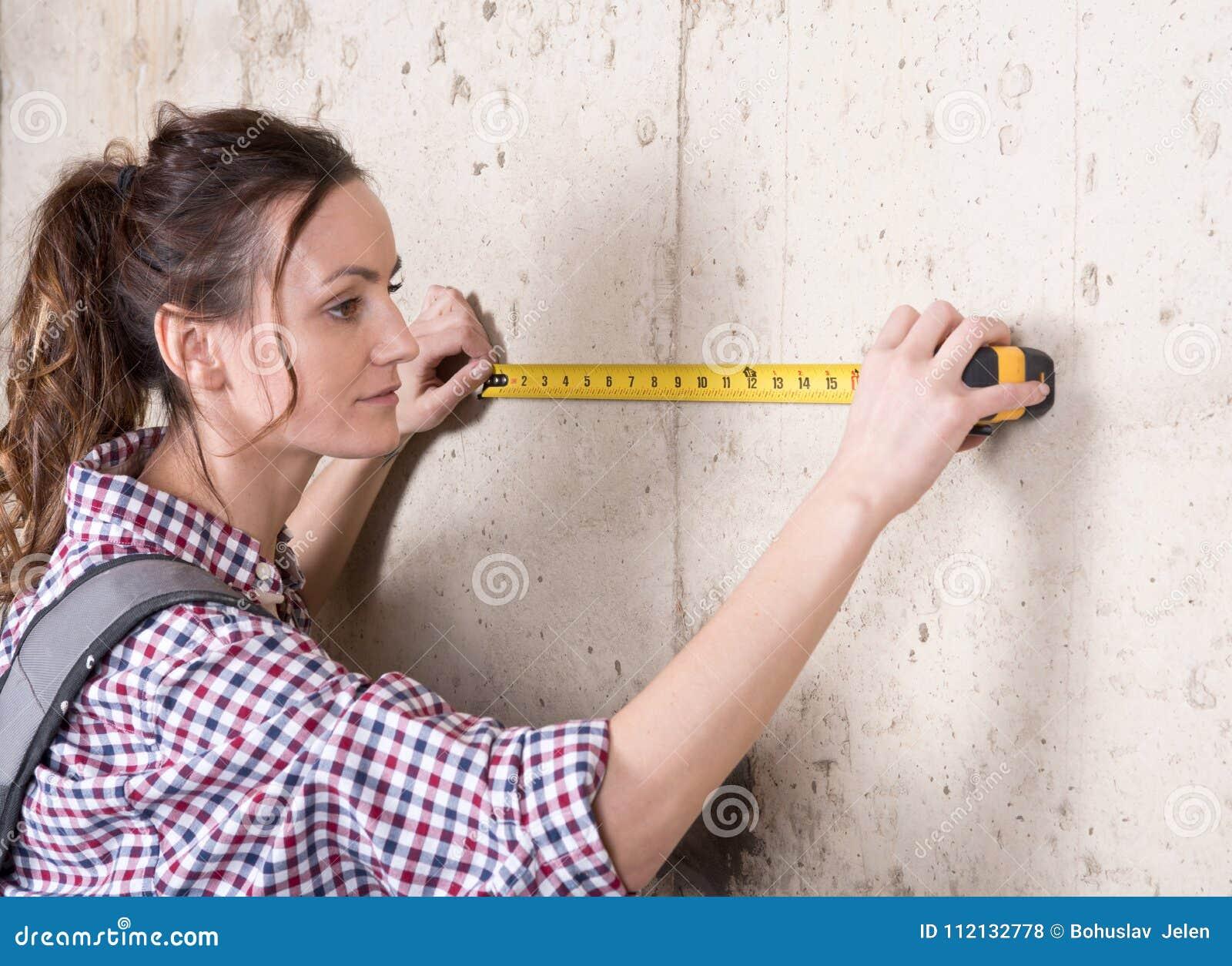 Молодая женщина работая с измеряя лентой