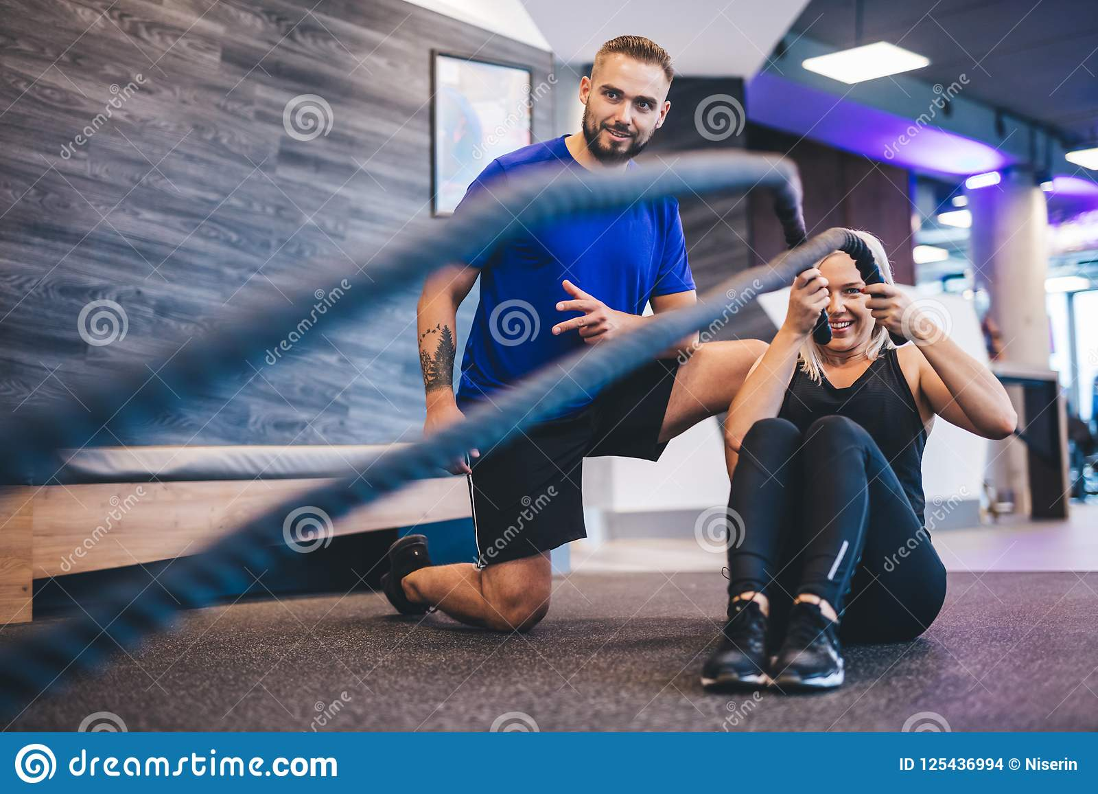 Молодая женщина работая с личным тренером на спортзале