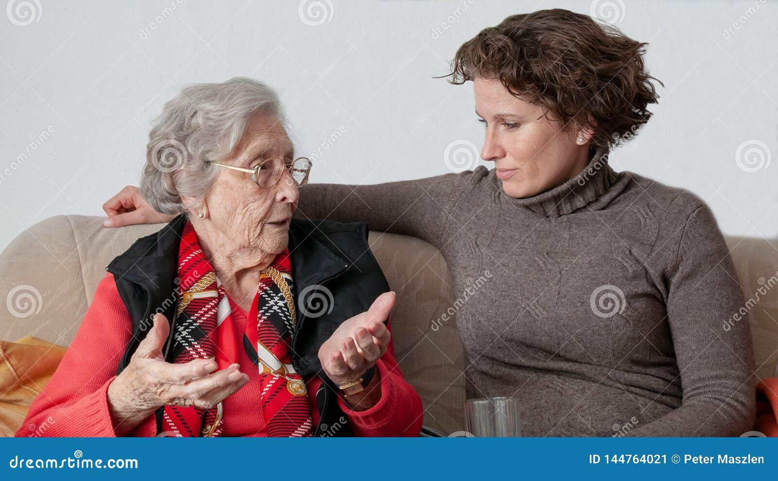 Молодая женщина разговаривая с грустной старшей женщиной