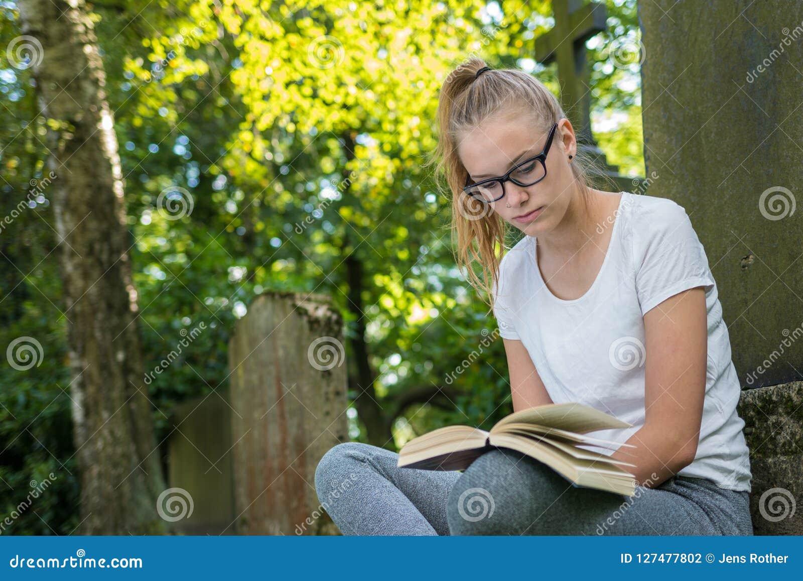 Молодая женщина сидит в парке и прочитала книгу