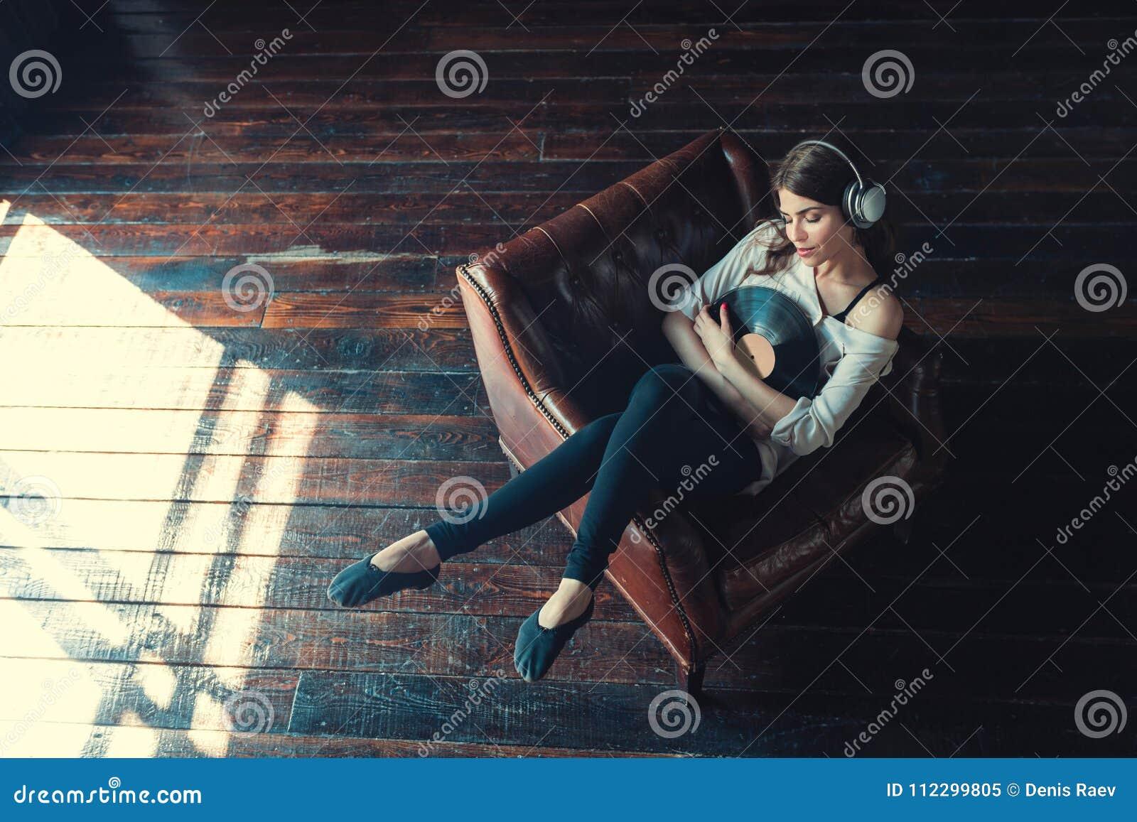 Молодая женщина слушает к музыке внутри помещения