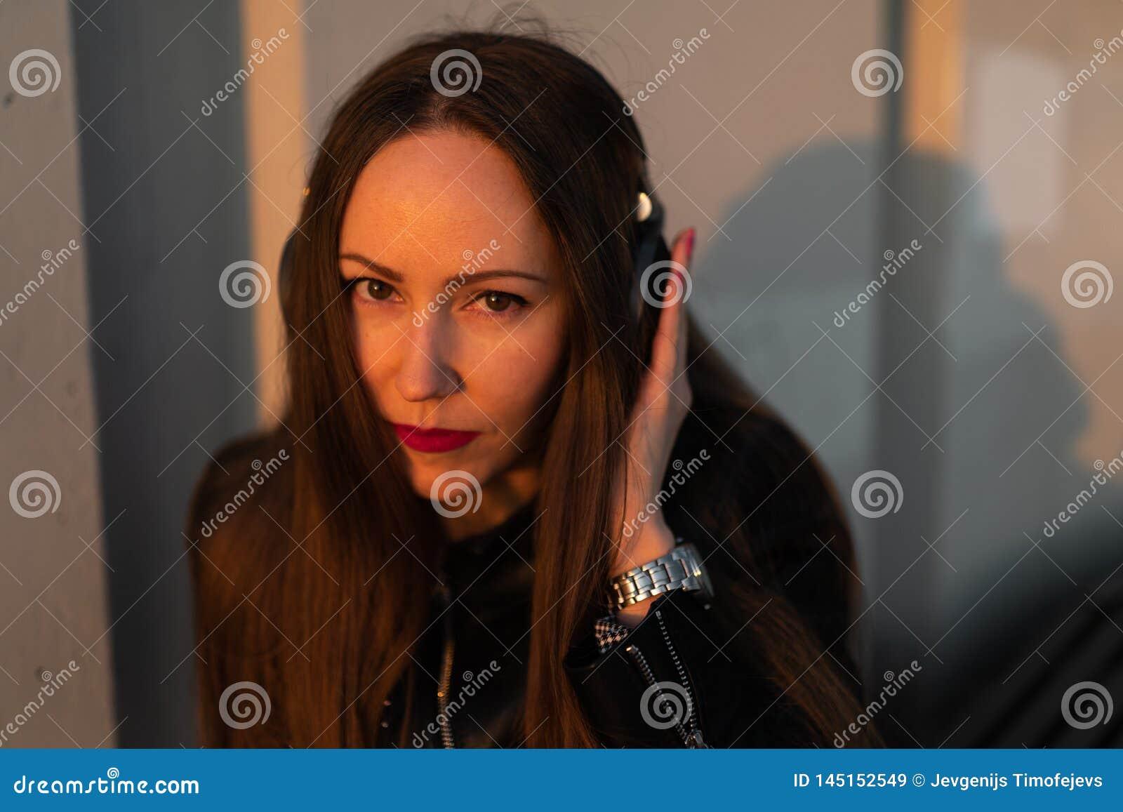Молодая женщина слушает музыку в закрытых наушниках через ее телефон