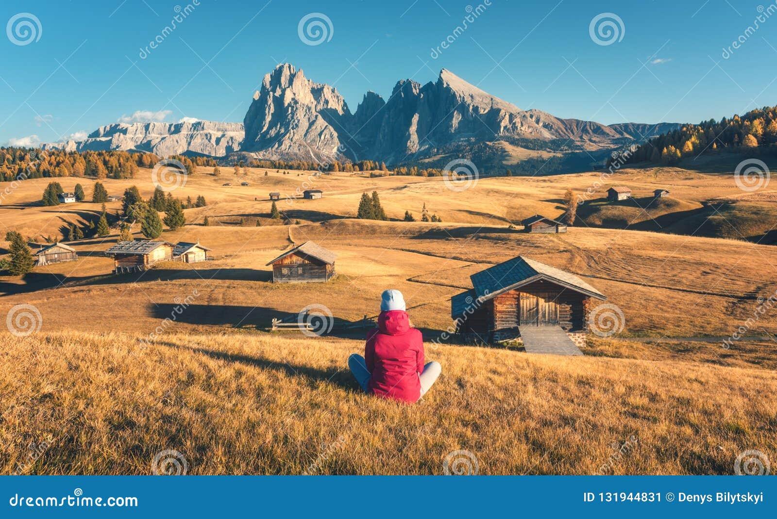 Молодая женщина смотря в лугах и горах на заходе солнца в осени