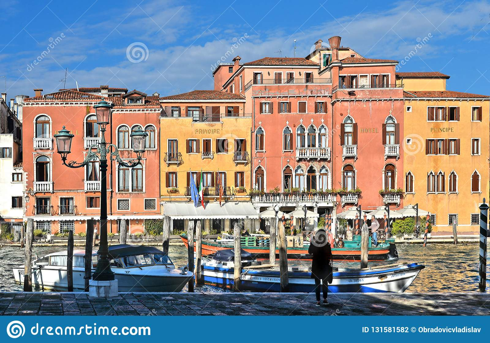 Молодая женщина смотря на канале большом со шлюпками гондолы, историческими красочными зданиями фасада, окнами и и architectu