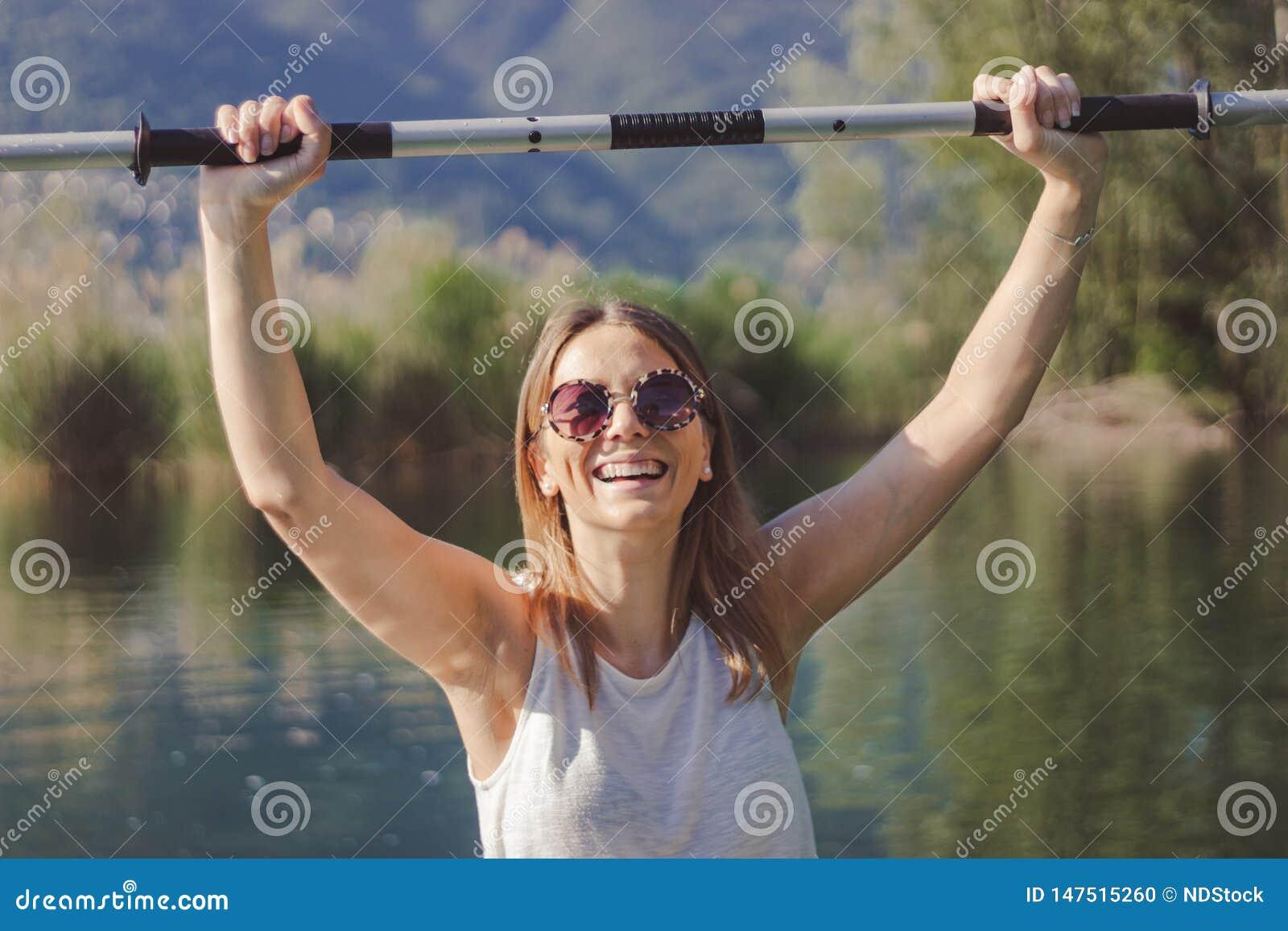 Молодая женщина сплавляясь на каяке на озере
