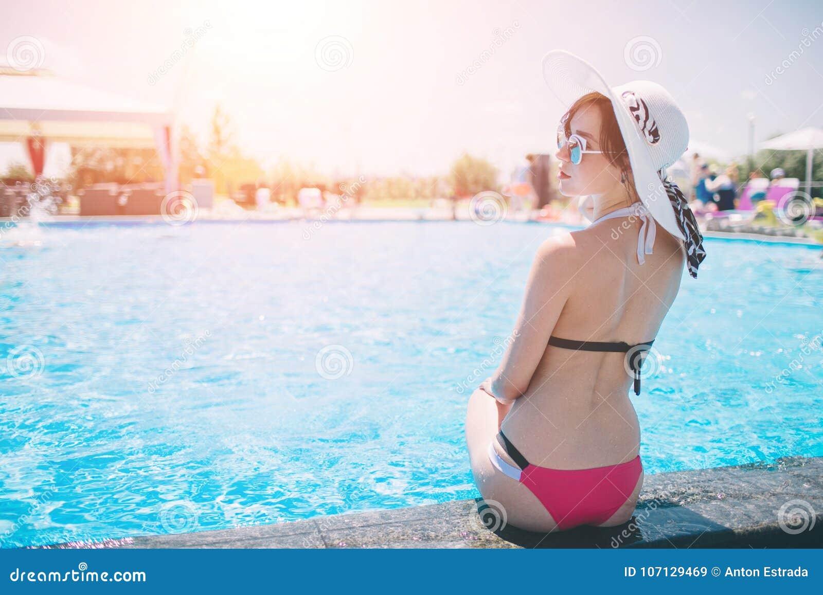 Молодая женщина счастливая в большой шляпе ослабляя на бассейне, перемещении около пляжа в заходе солнца лето концепции