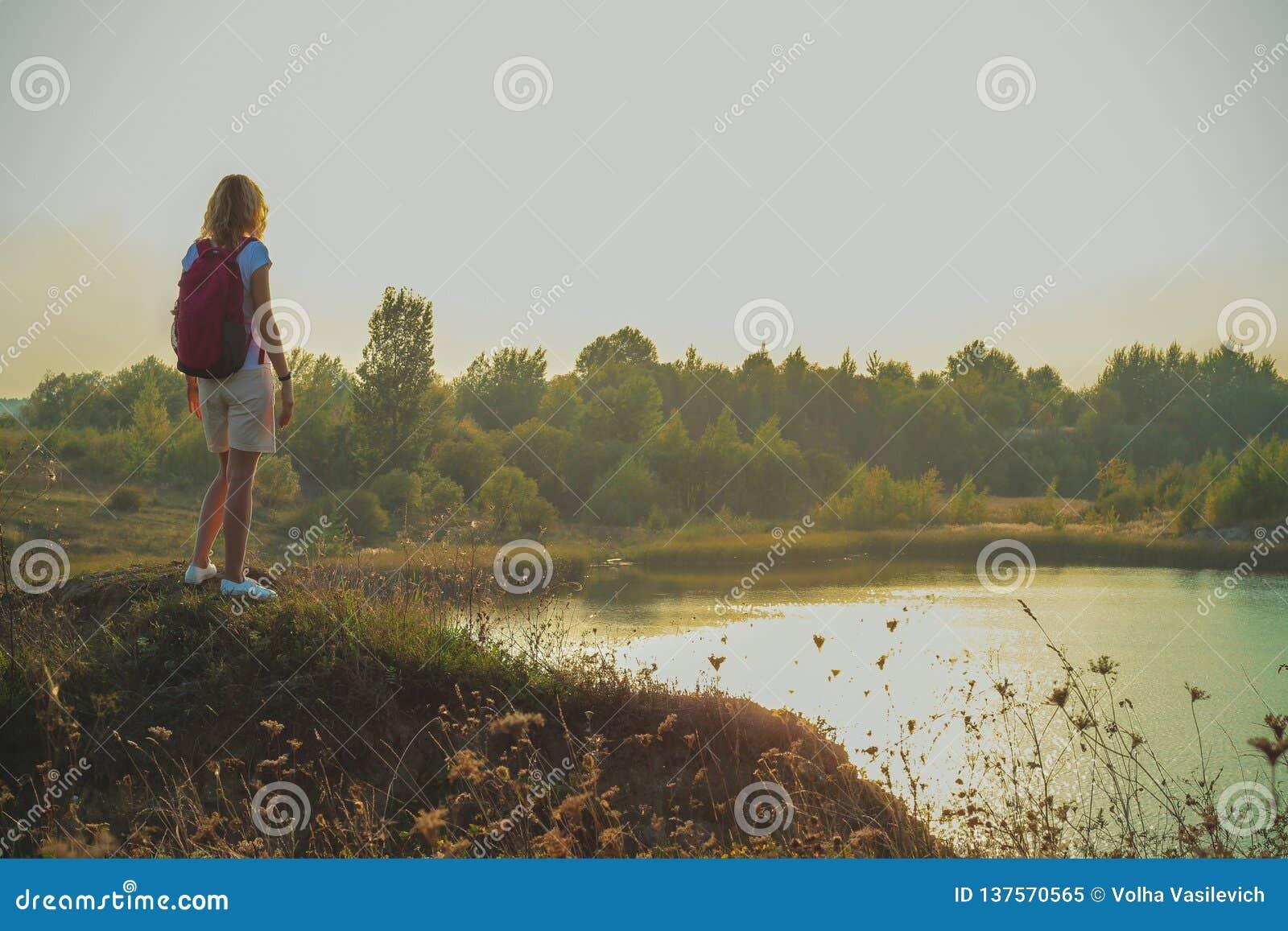 Молодая женщина с розовым рюкзаком стоит на голубом конце предпосылки карьеров мела вверх во времени захода солнца