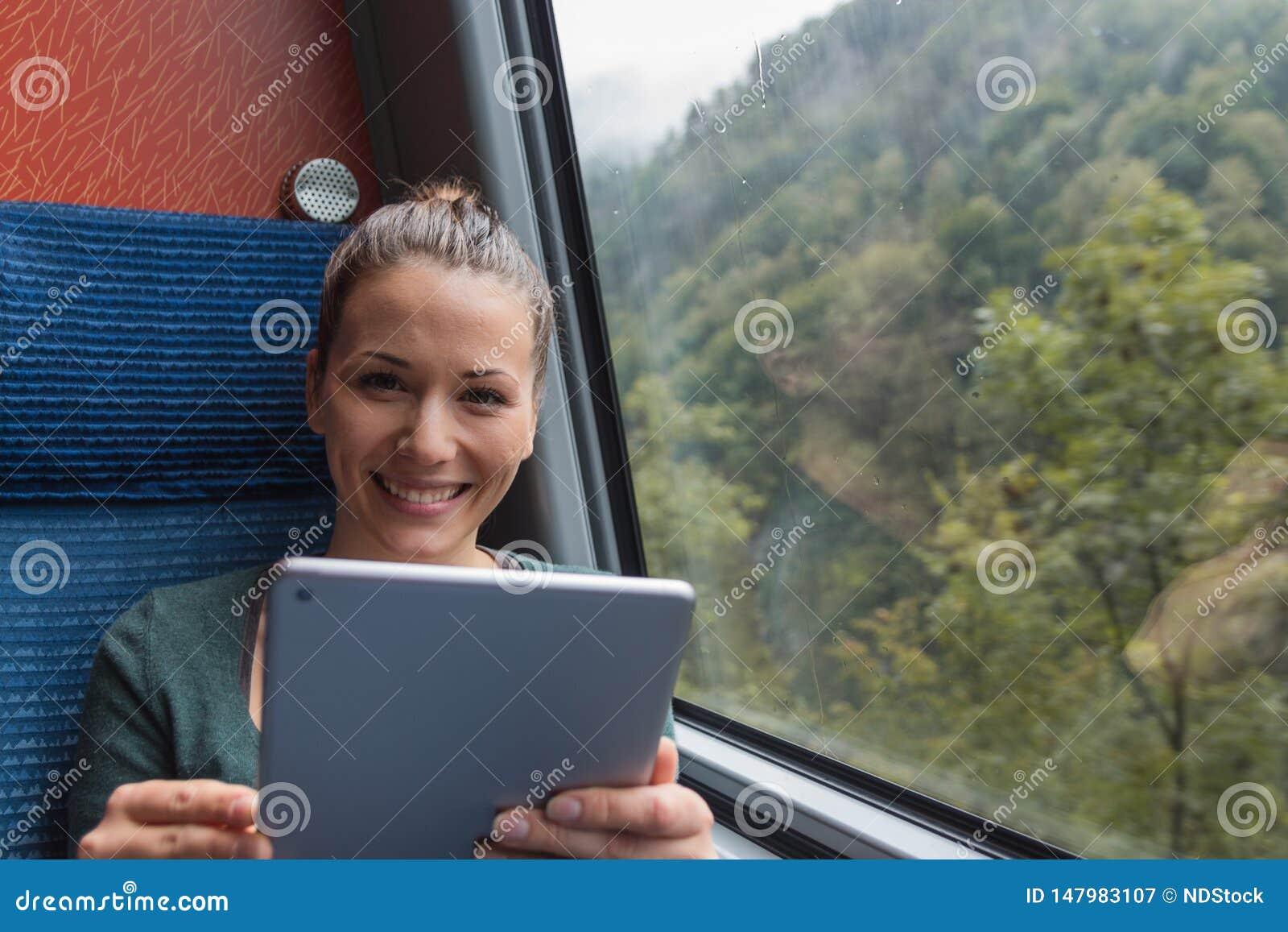 Молодая женщина усмехаясь и используя планшет для изучать пока путешествующ поездом