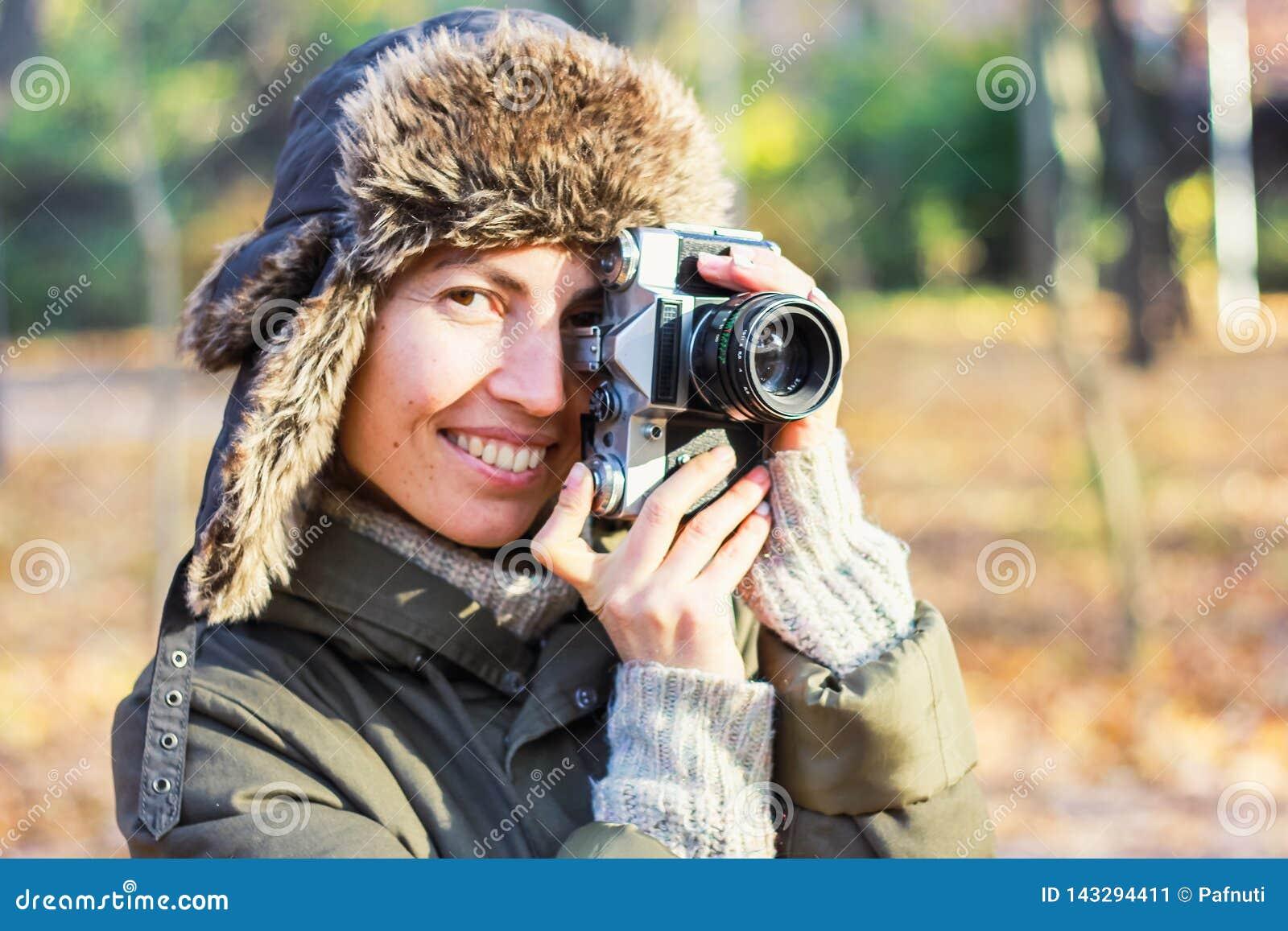 Молодая женщина фотографируя в парке осени