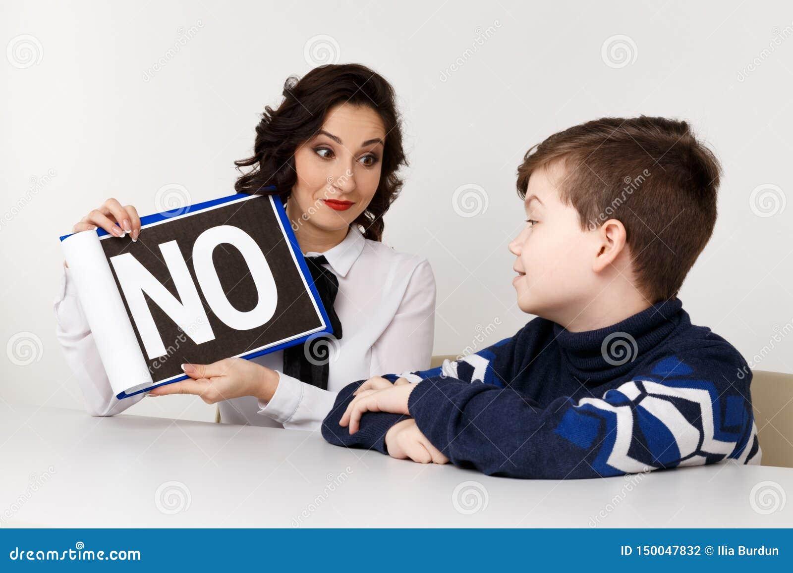 Молодая женщина brunnette говоря с мальчиком крытым белую комнату Женщина психолога с patiant Терапия психологии
