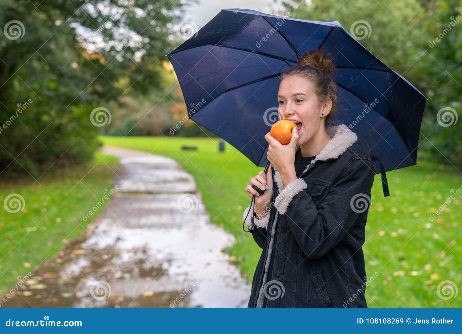Молодая женщина Smilling есть яблоко outdoors
