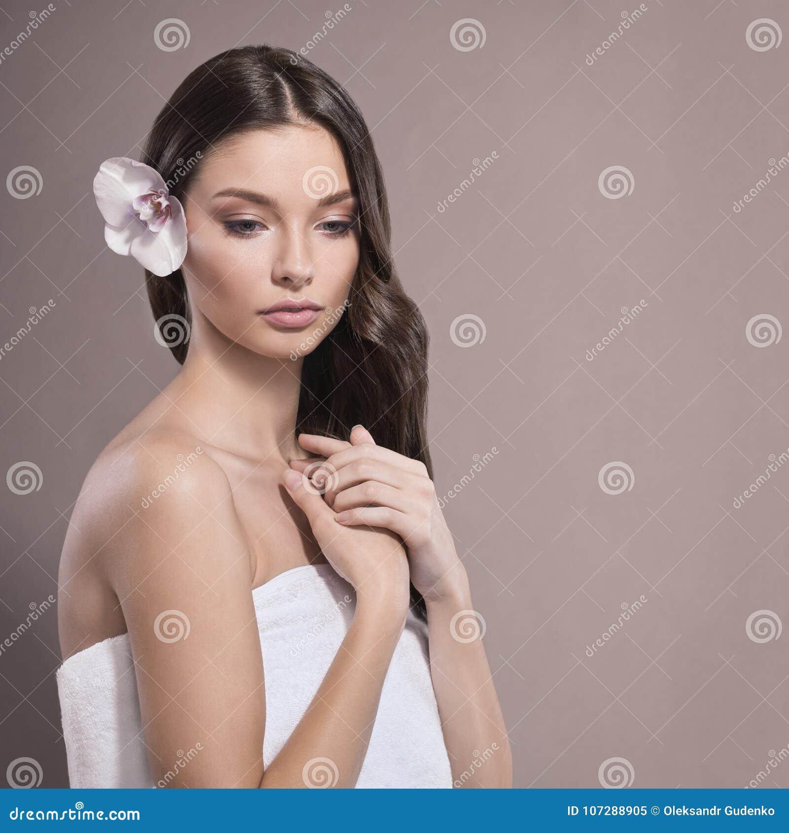 Молодая и здоровая женщина с светлым составом и цветком орхидеи Бежевая предпосылка