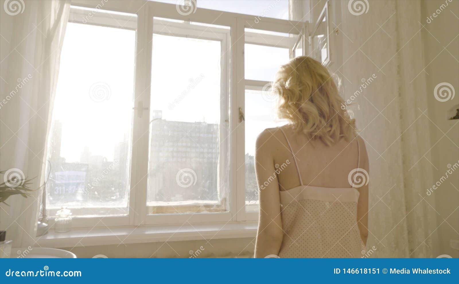 Сексуальная блондинка возле окна