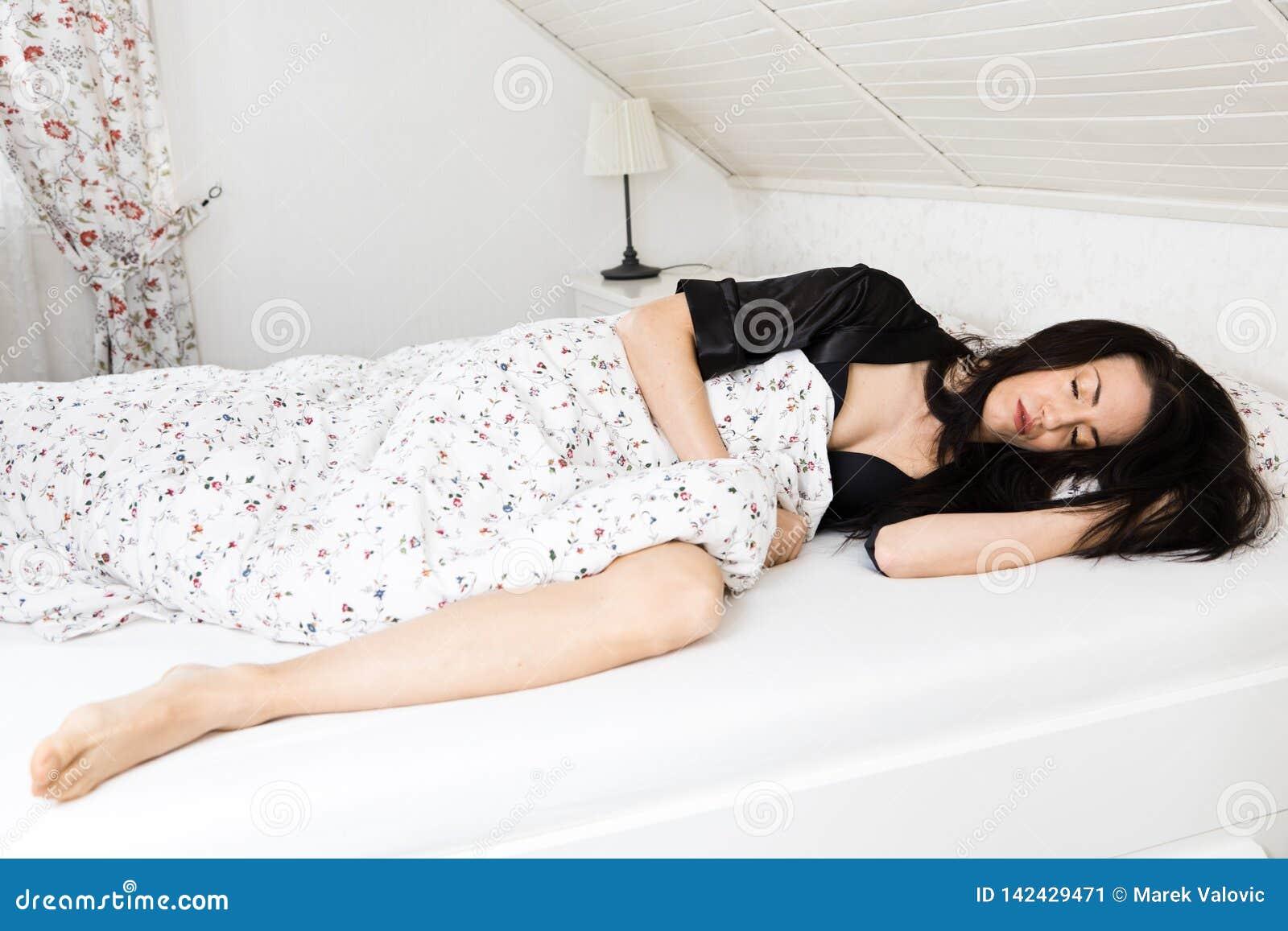 Молодая и красивая женщина спать в кровати в черном халате