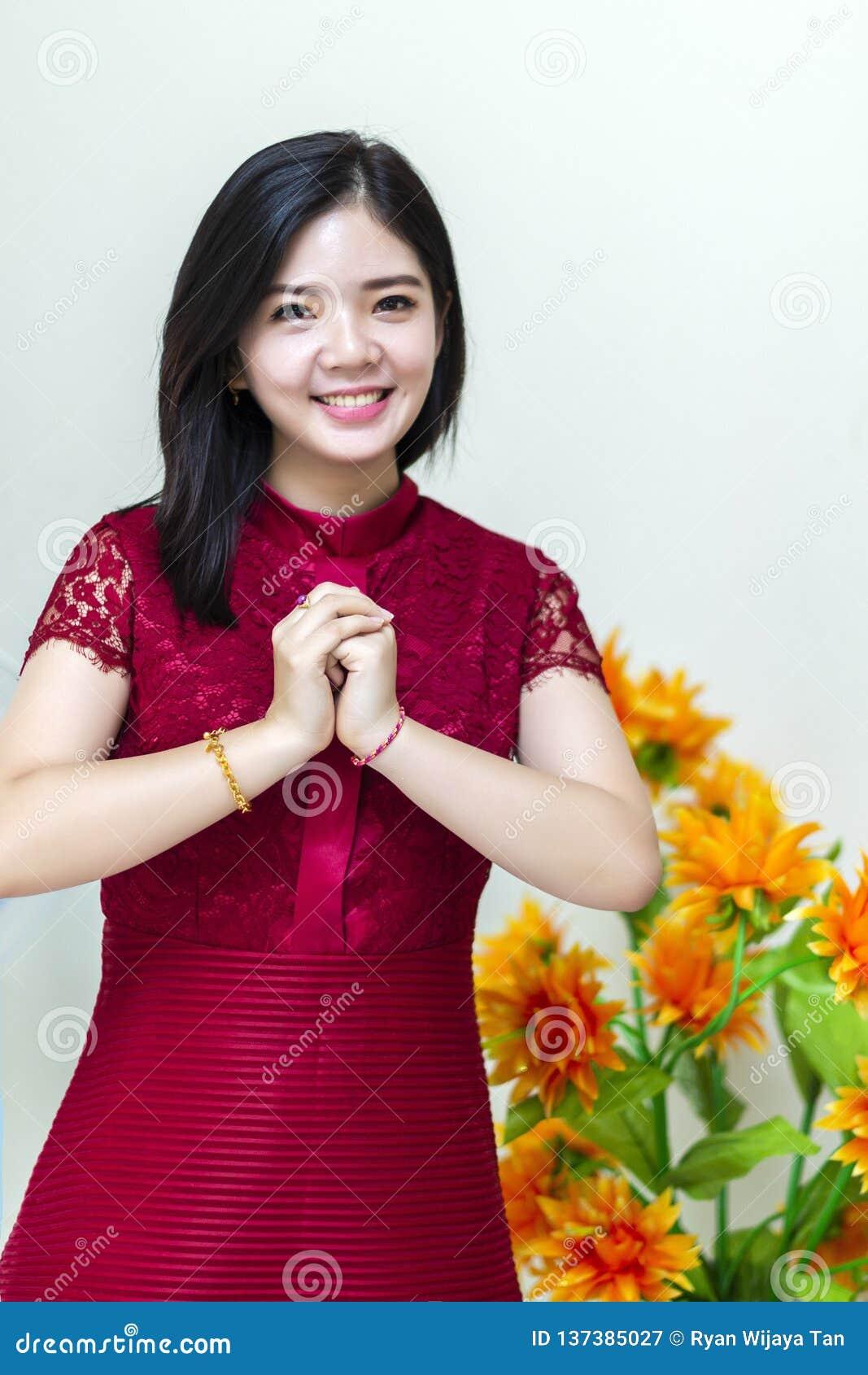 Молодая и красивая китайская девушка желая гонг XI Fa Chai дома